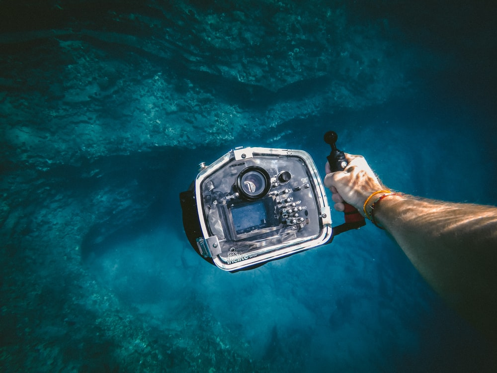 person holding underwater camera
