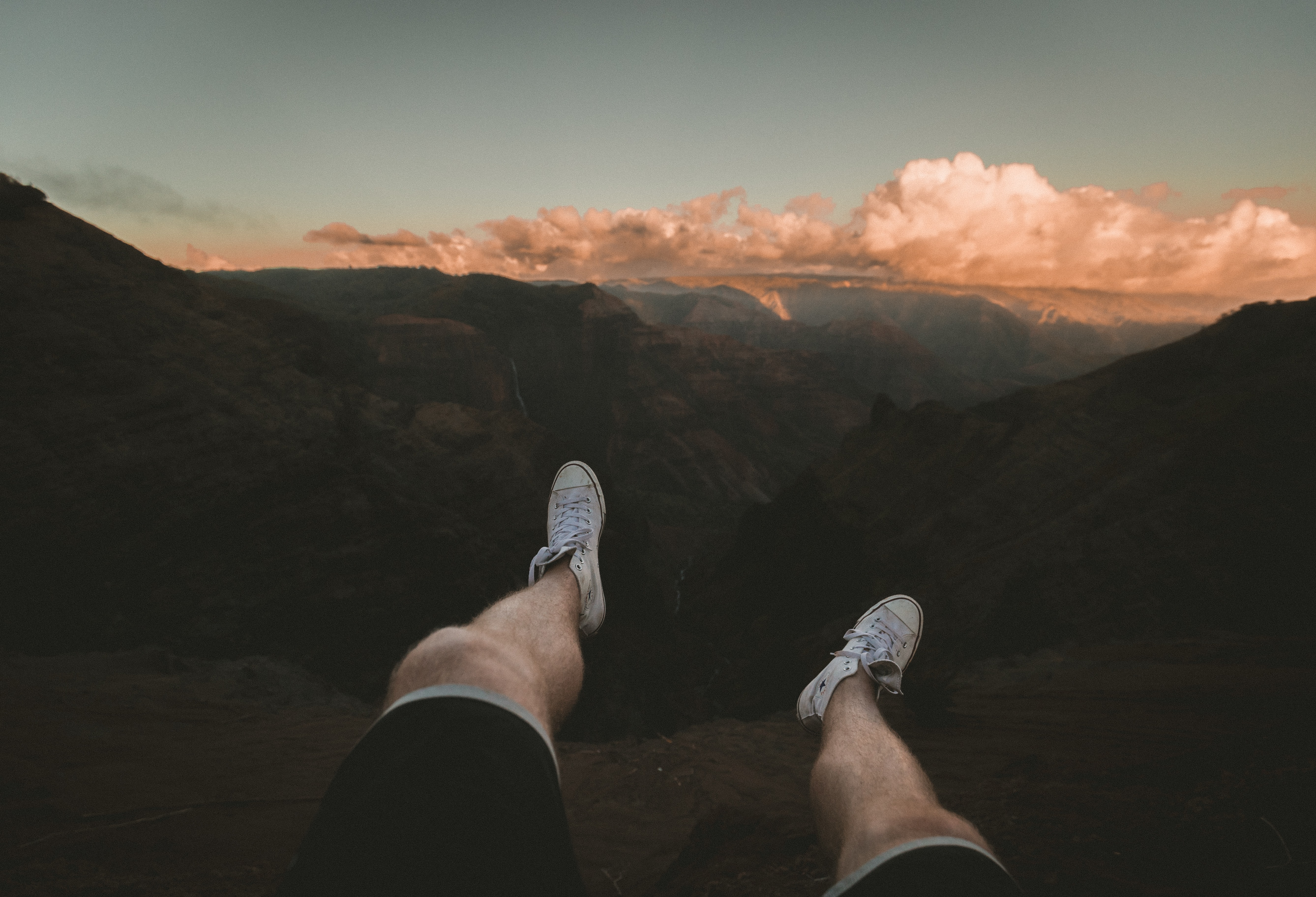 Legs outstretched into a mountain canyon at sunset