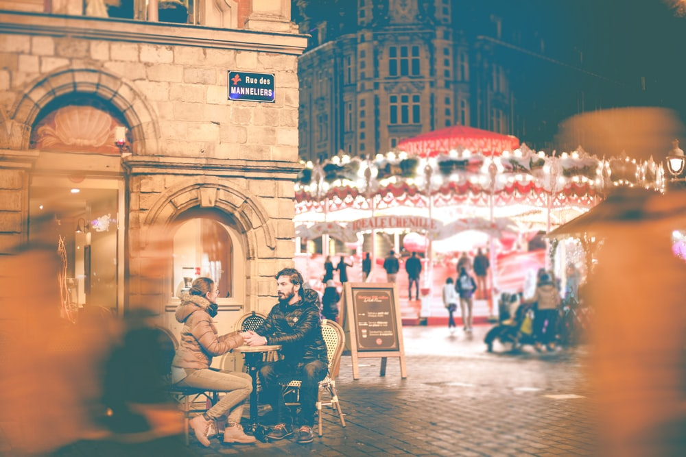 couple sitting beside building near carousel during night time