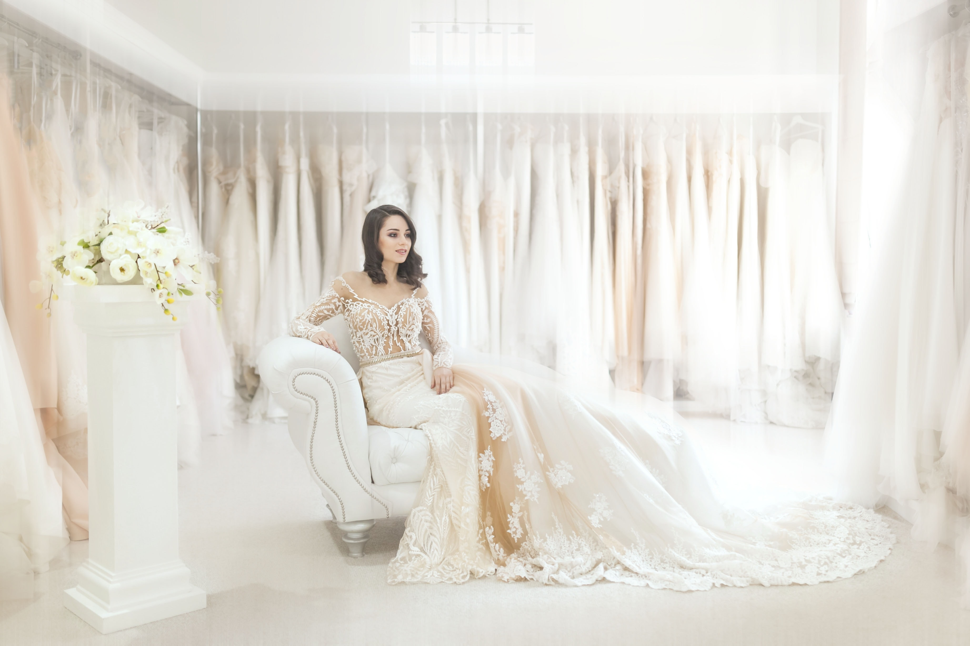 A woman in a bridal dress sitting on a white leather armchair in a white room