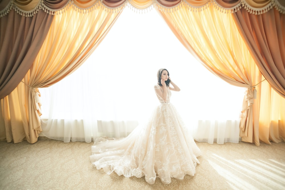 photo of woman wearing white gown near window curtain