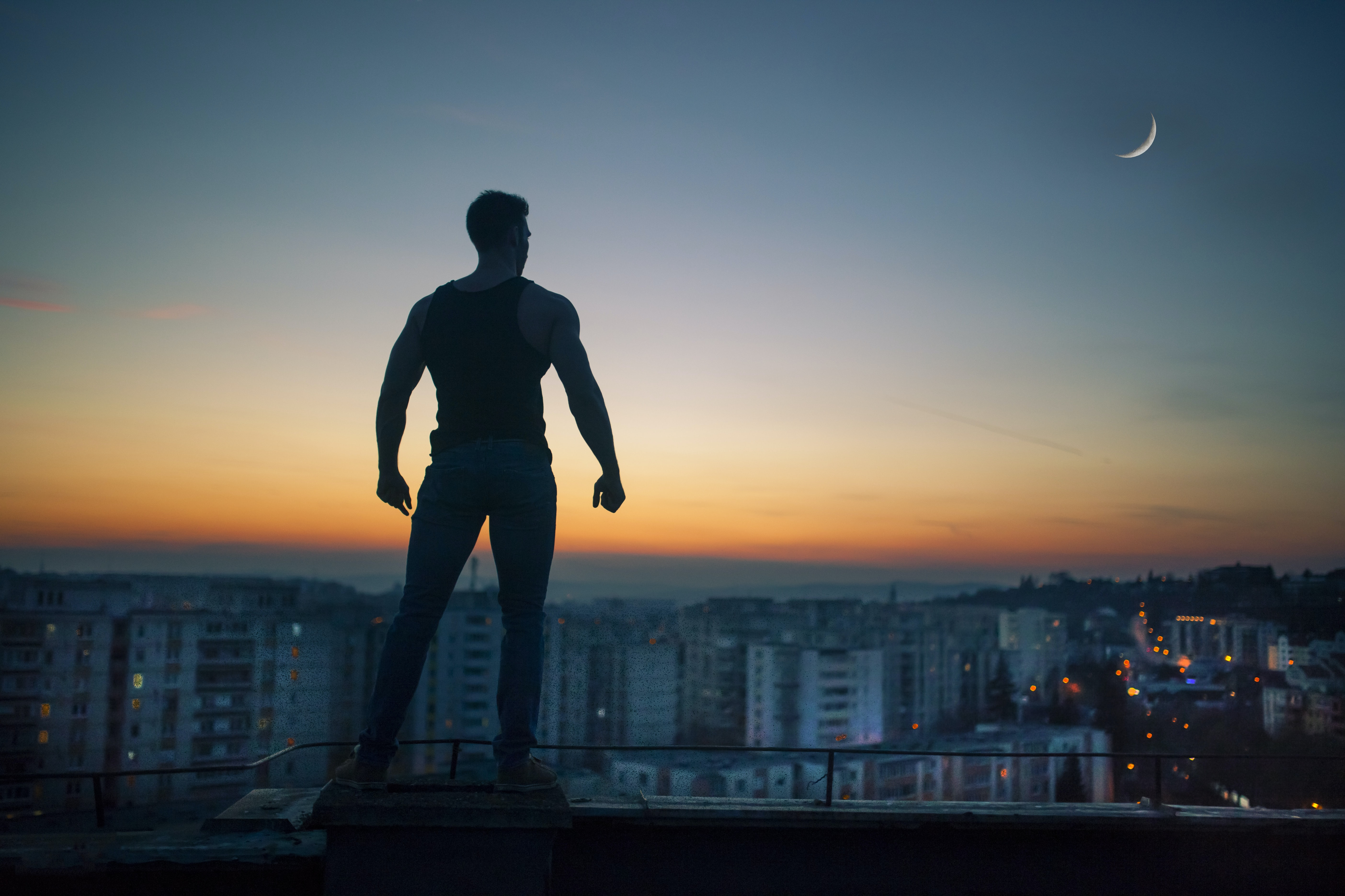 A silhouette of a man standing on a building roof and looking of into the city at sunset