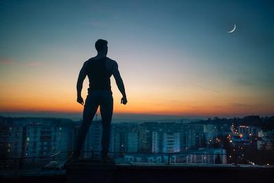 夕焼け空のビルの屋上で立っている男性の影