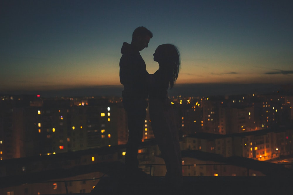 silhouette of man and woman standing on roof building