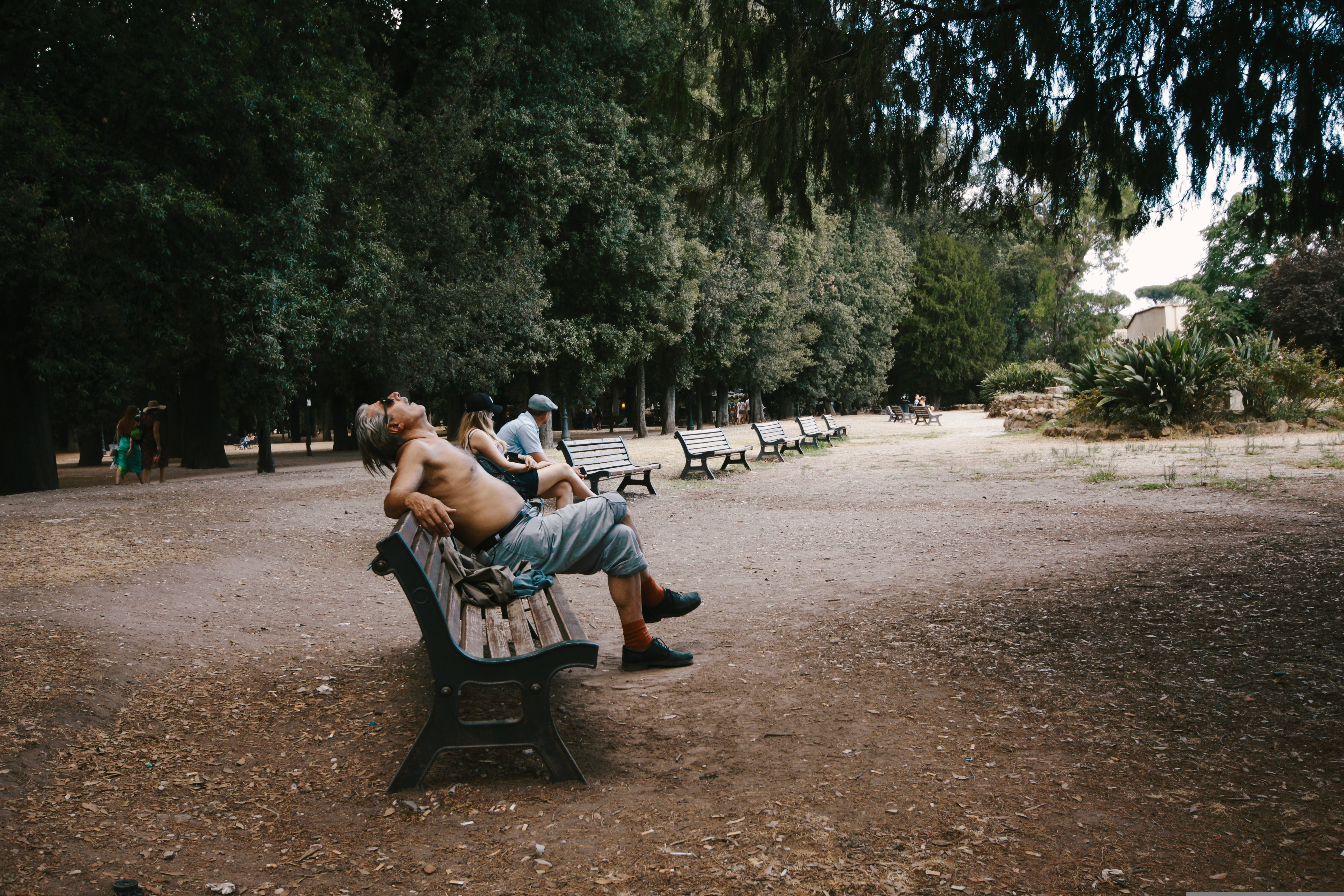 A shirtless man sitting on a bench, sleeping in a park at Villa Borghese