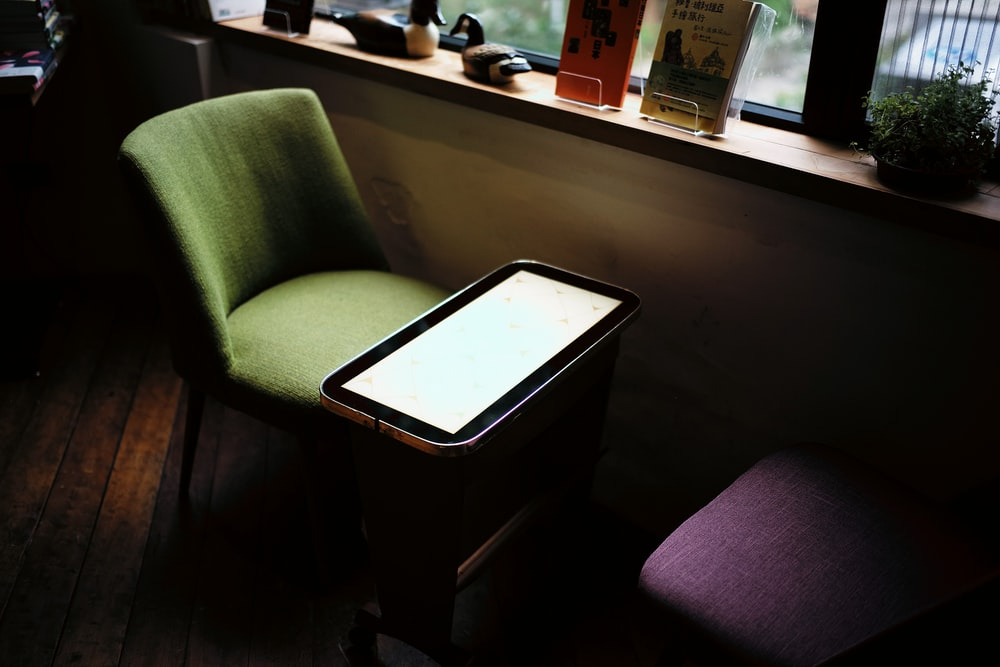 green chair in front of table near window