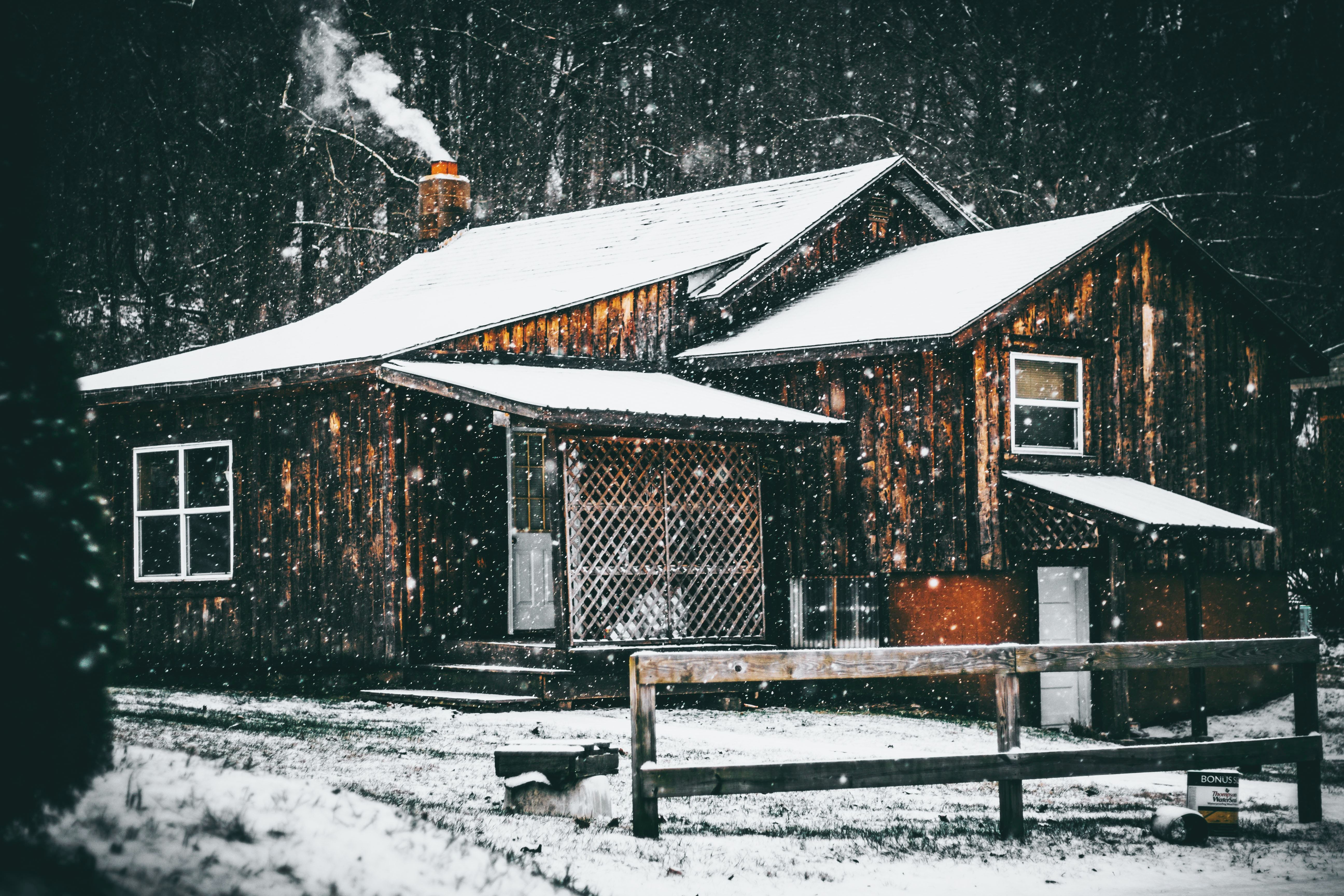 A cabin in the woods during the winter with snow over the roof