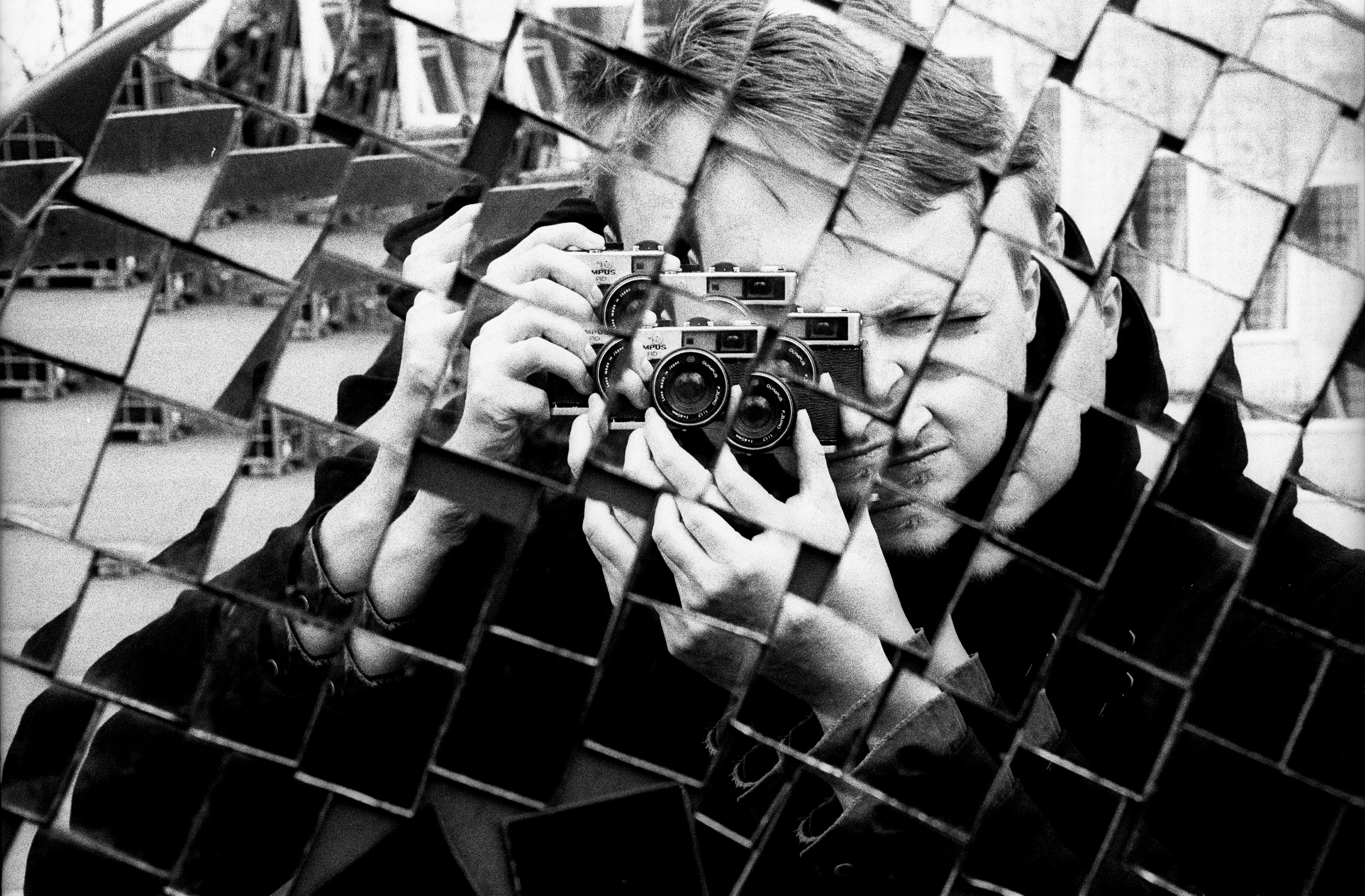 Black and white shot of man's reflection holding camera taking photo in textured mirror, Teufelsberg