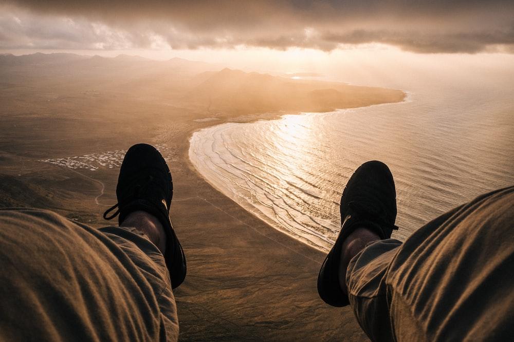person sitting on cliff near ocean