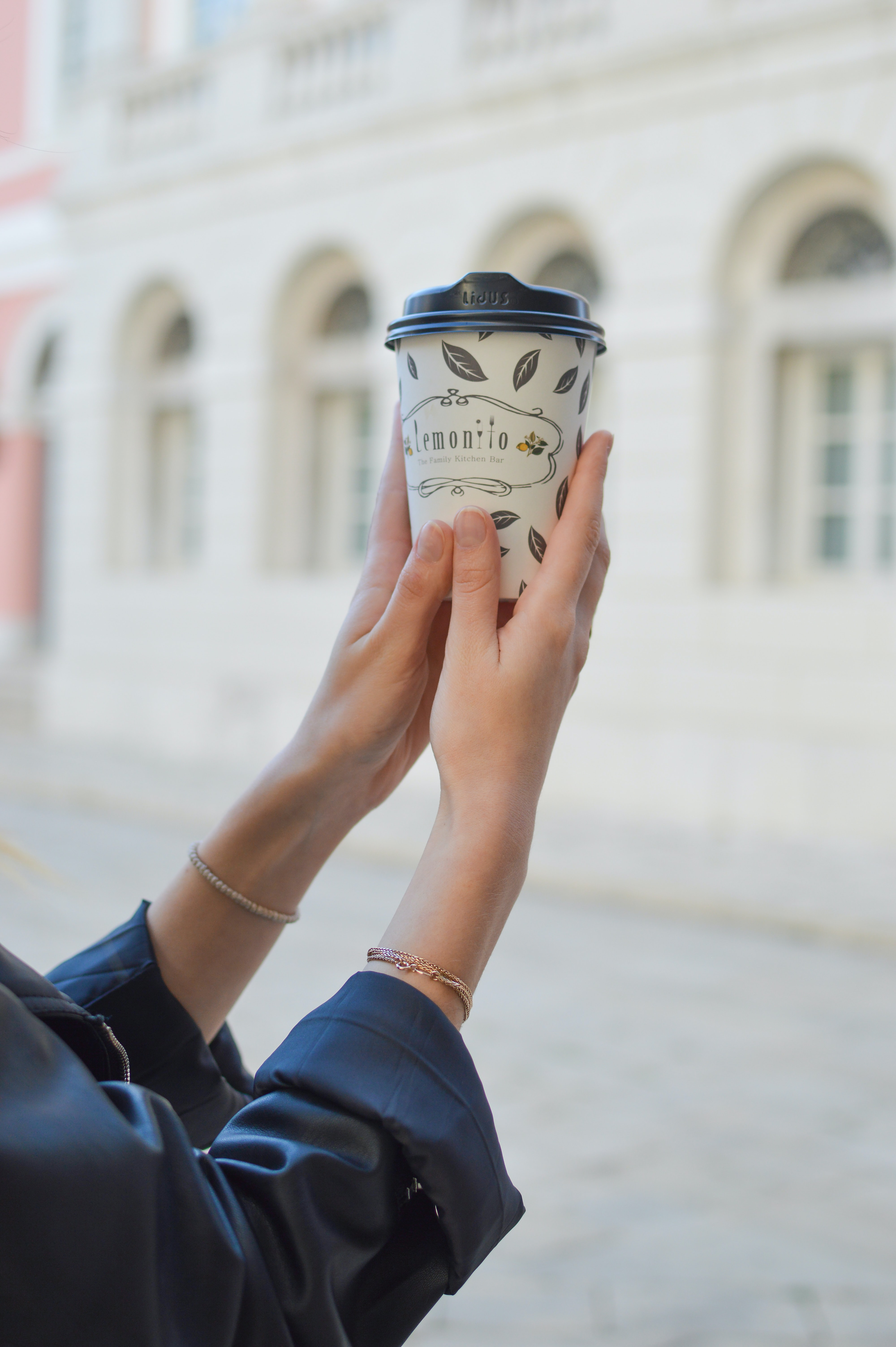 A woman holding up a takeaway coffee cup