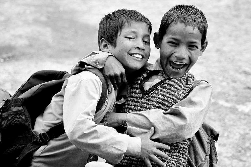 grayscale photography of two boys hugging while laughing