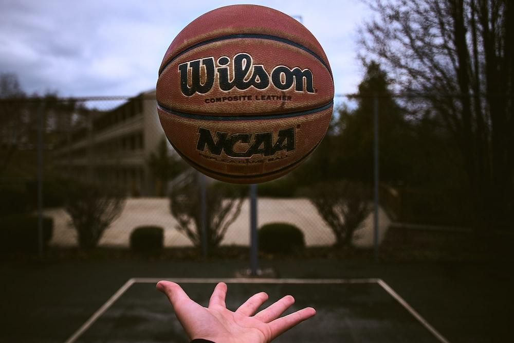 person releasing orange Wilson basketball ball