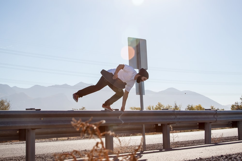 man crossing on road fence while holding black skateboard