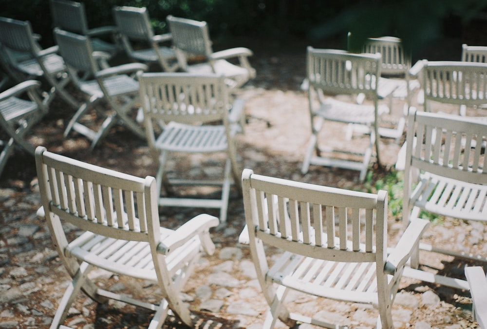 empty white wooden folding chairs