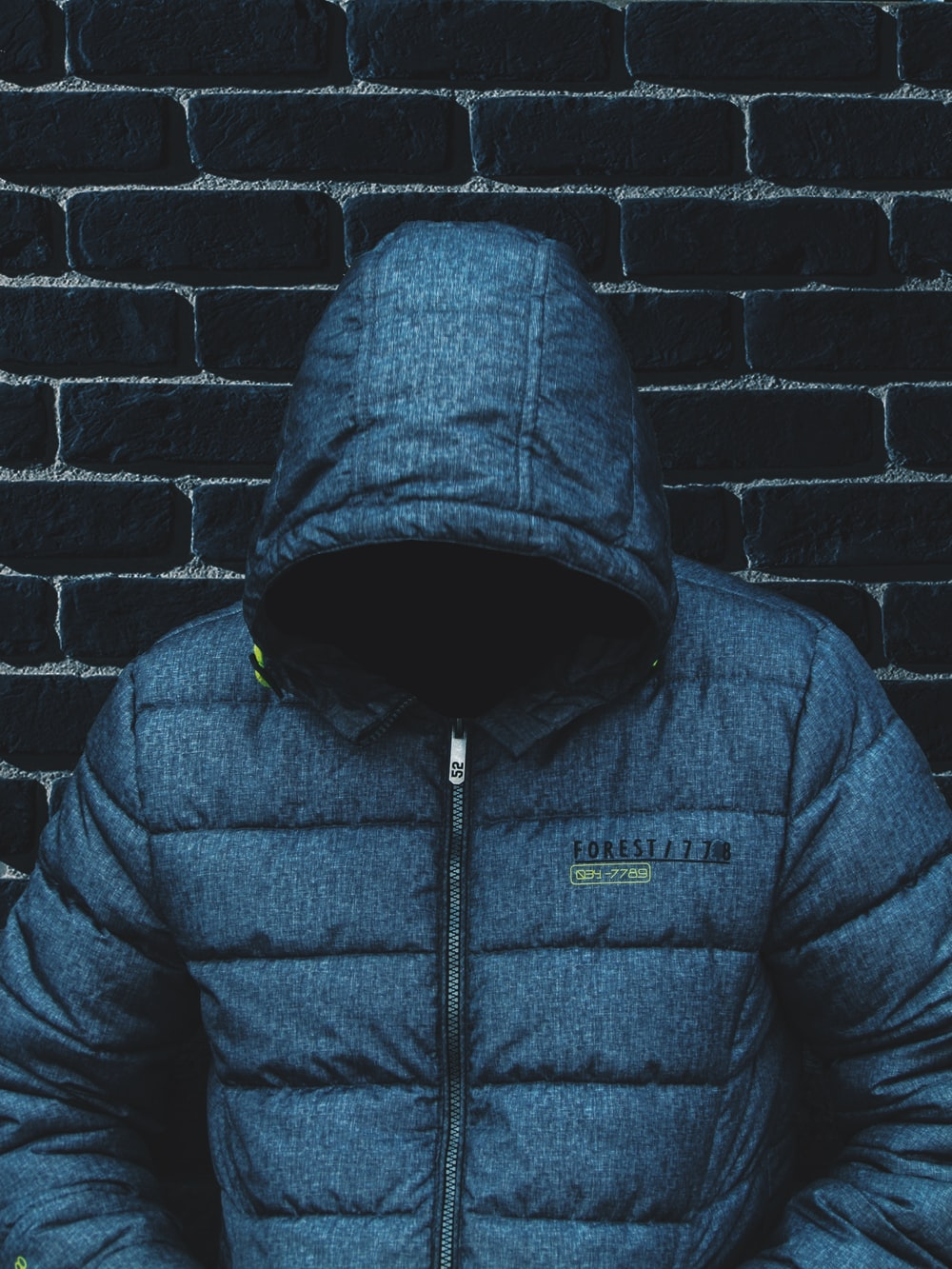 person with head down wearing blue zip-up jacket leaning on wall