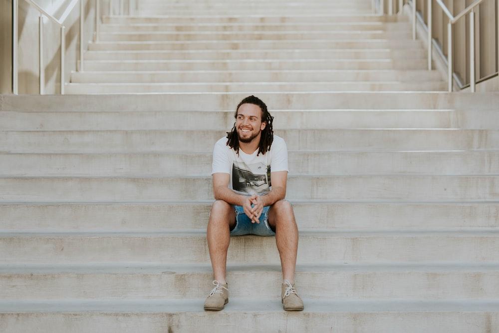 smiling man sitting on staircase