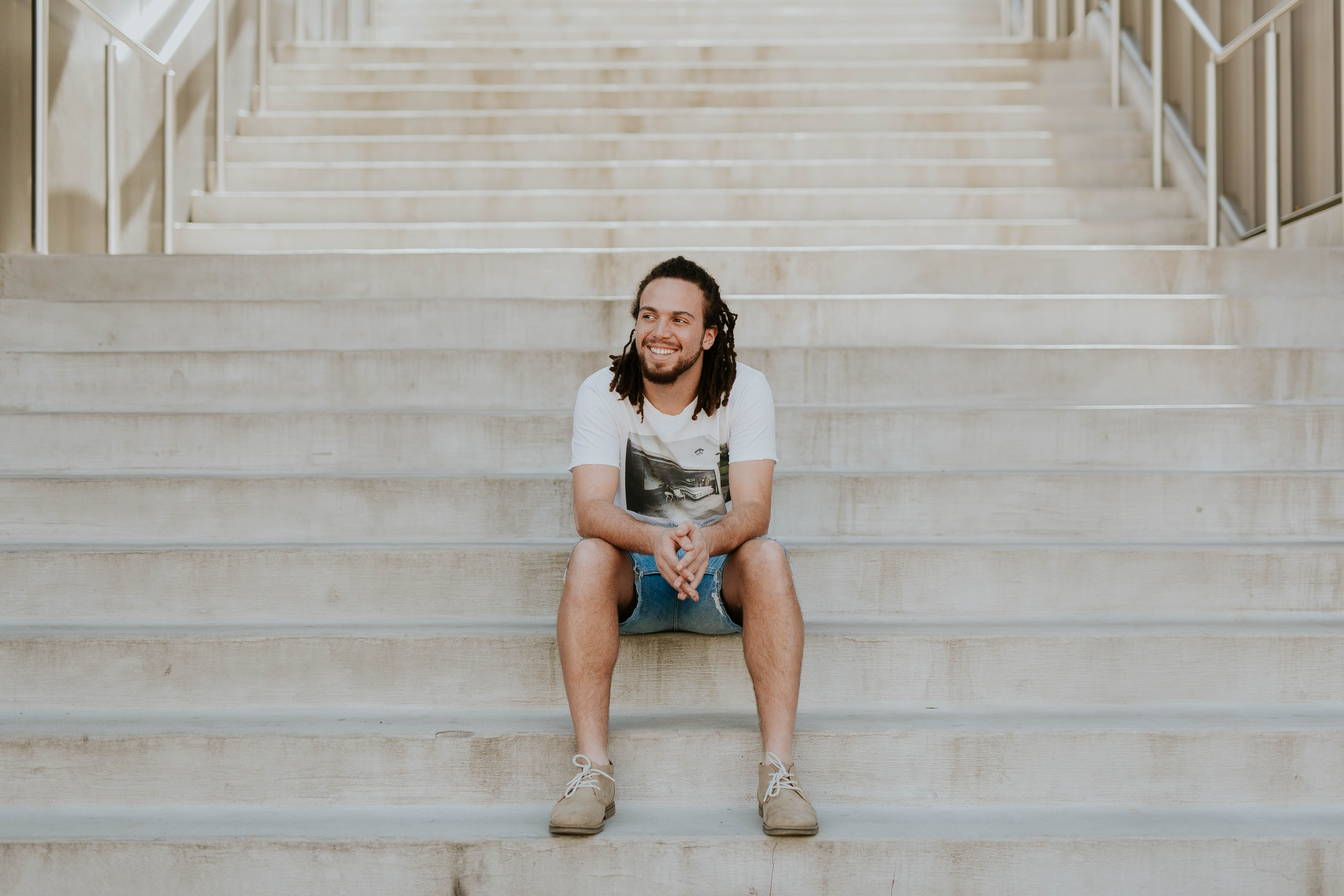 smiling man sitting on staircase