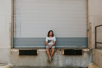 man sitting on pavement in front of roller shutter