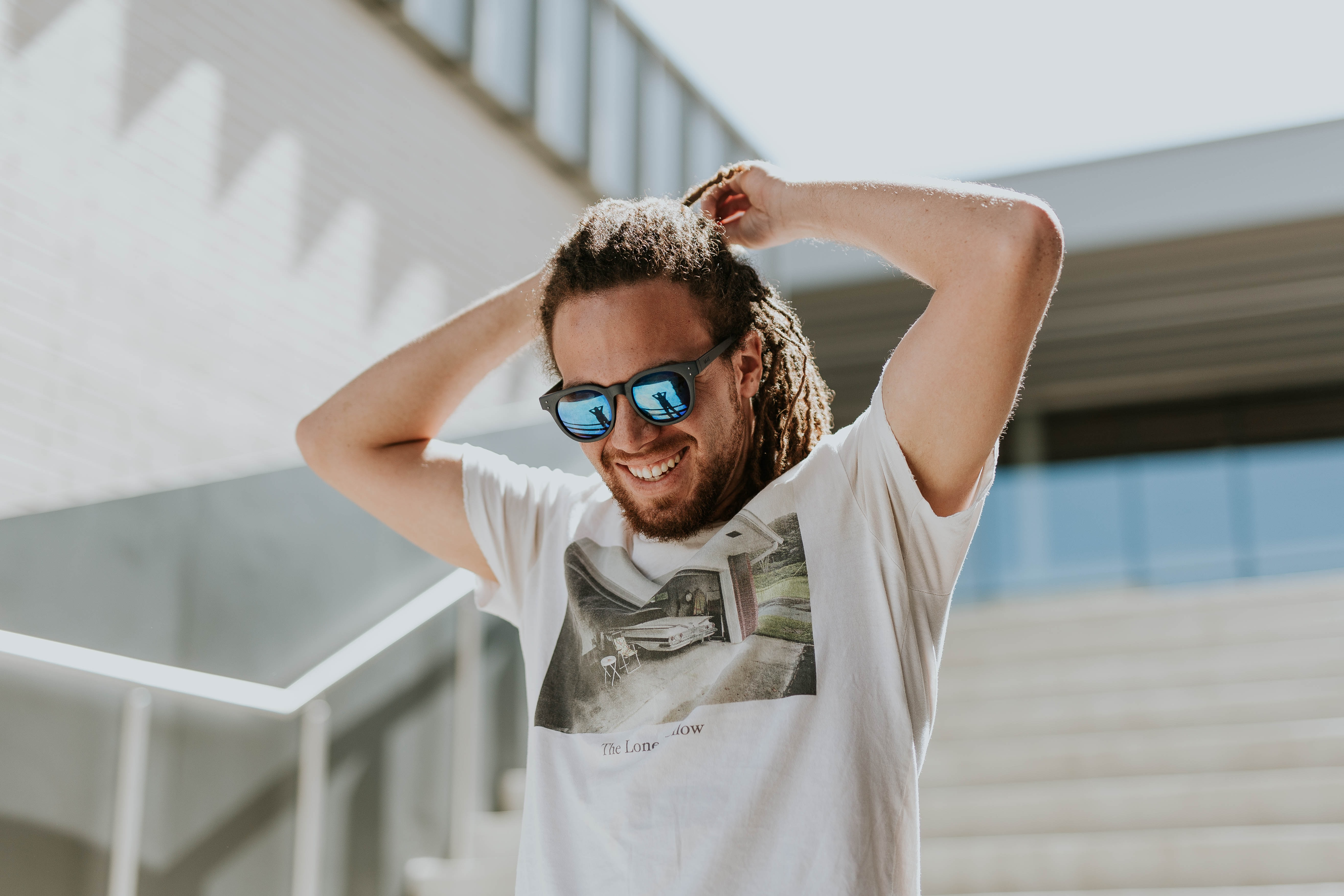A smiling man wearing sunglasses and dreadlocks holds his hands atop his head on the stairs