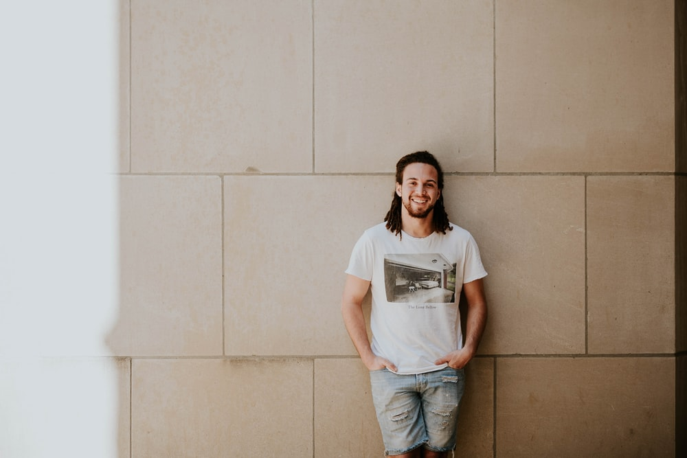 man leaning on white wall