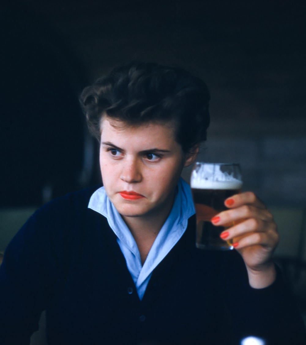 man sitting while holding glass of beer