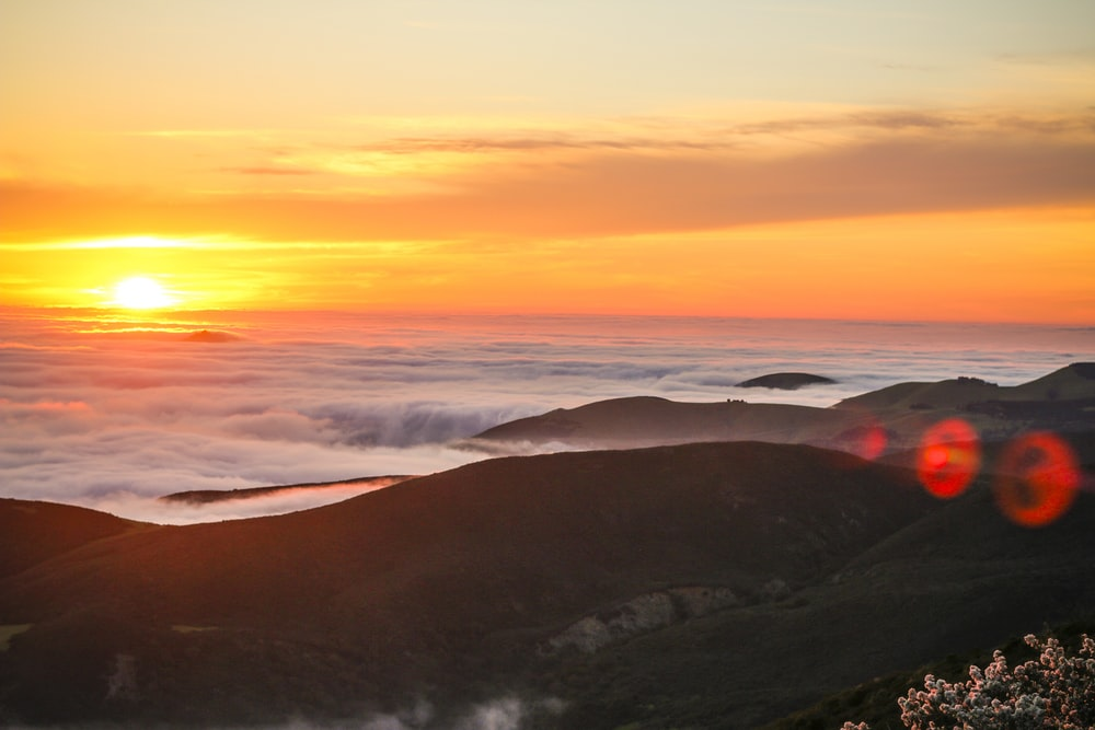 sun over the clouds and hill