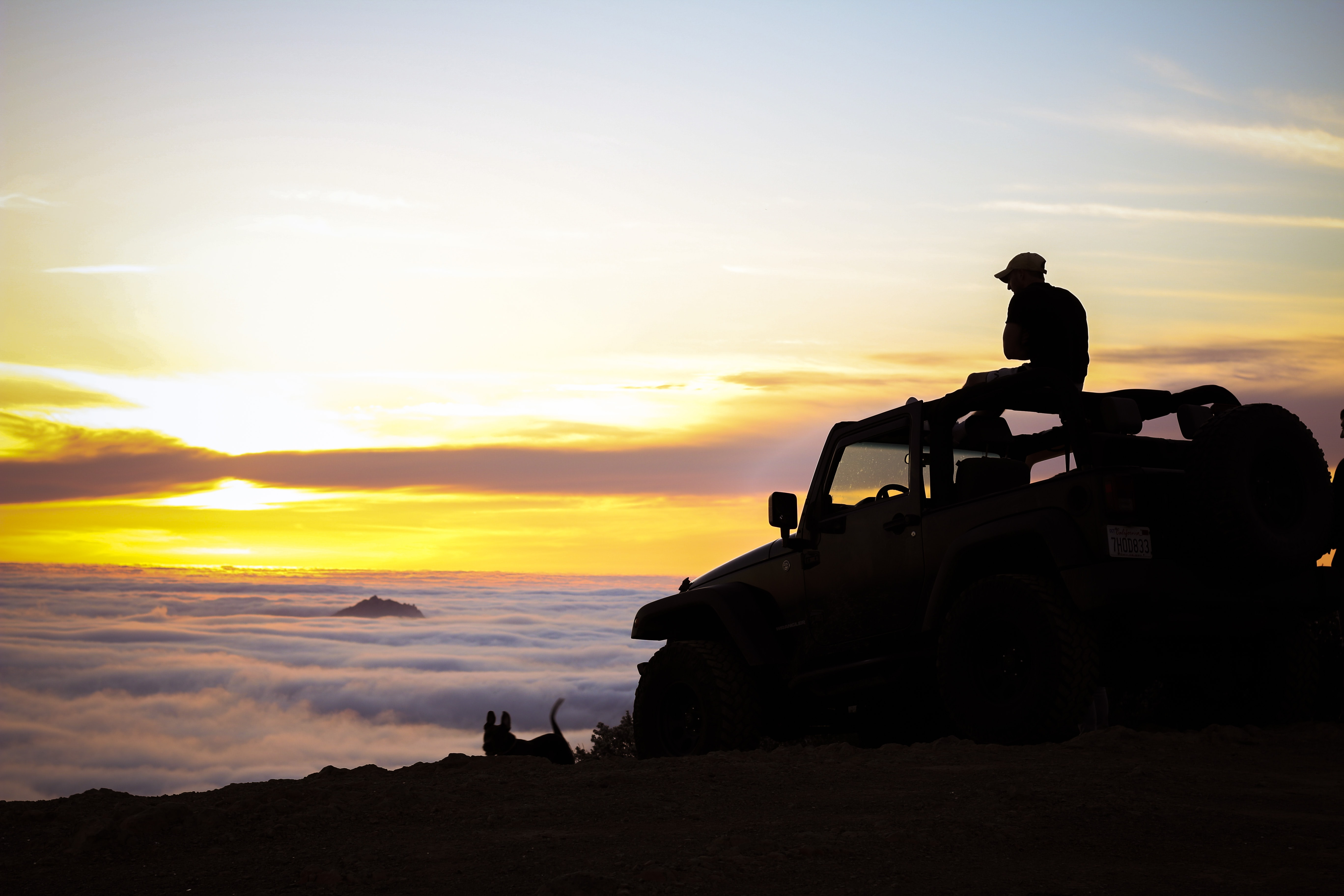 A silhouette of a person sitting on a jeep and watching the sunset above clouds