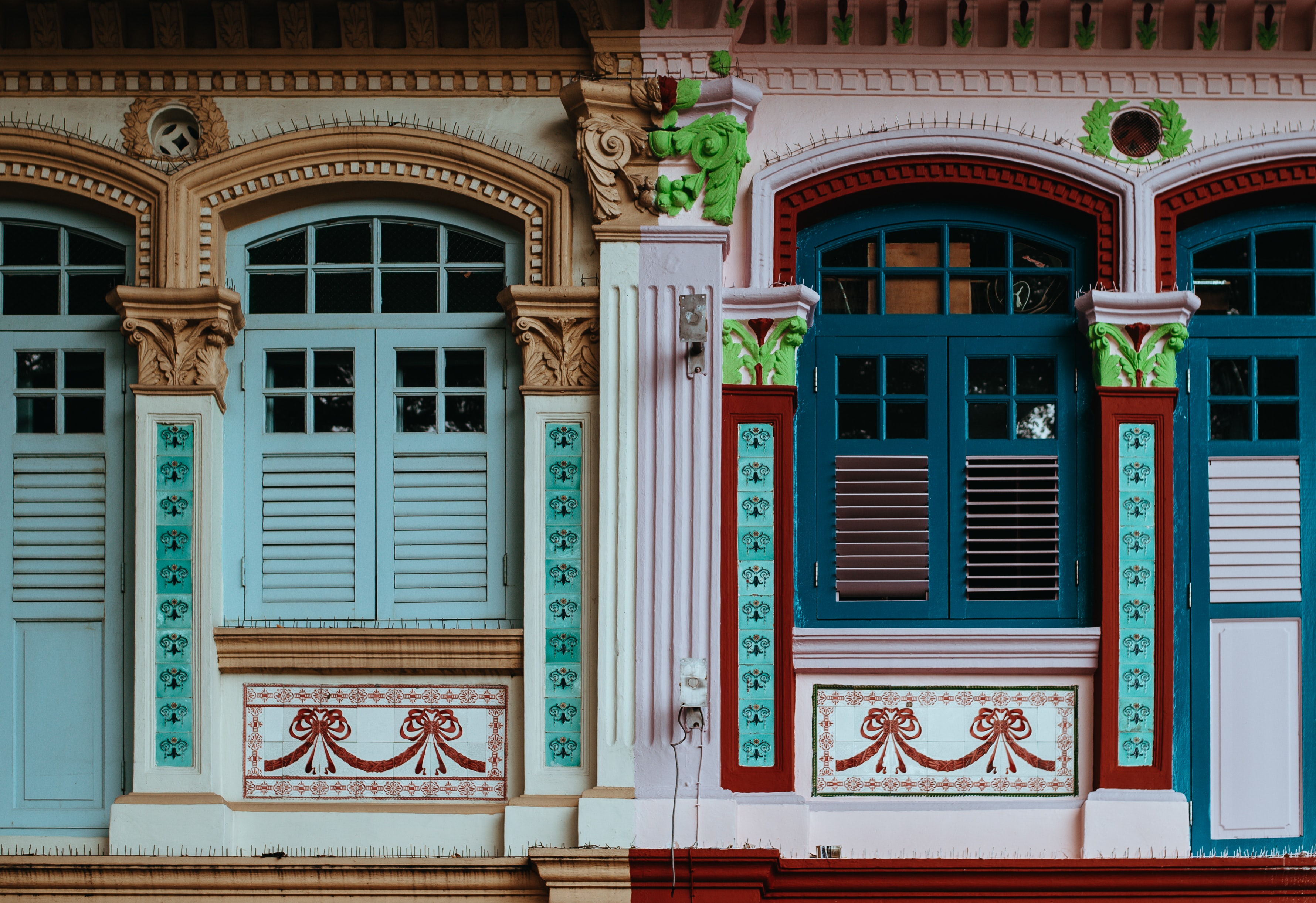 Colorful house windows with decorative pillars between them