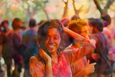 smiling woman holding her head and hair during daytime holi zoom background