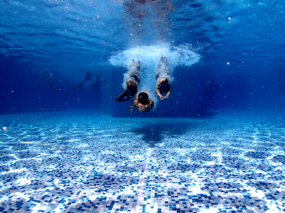 three person diving on water