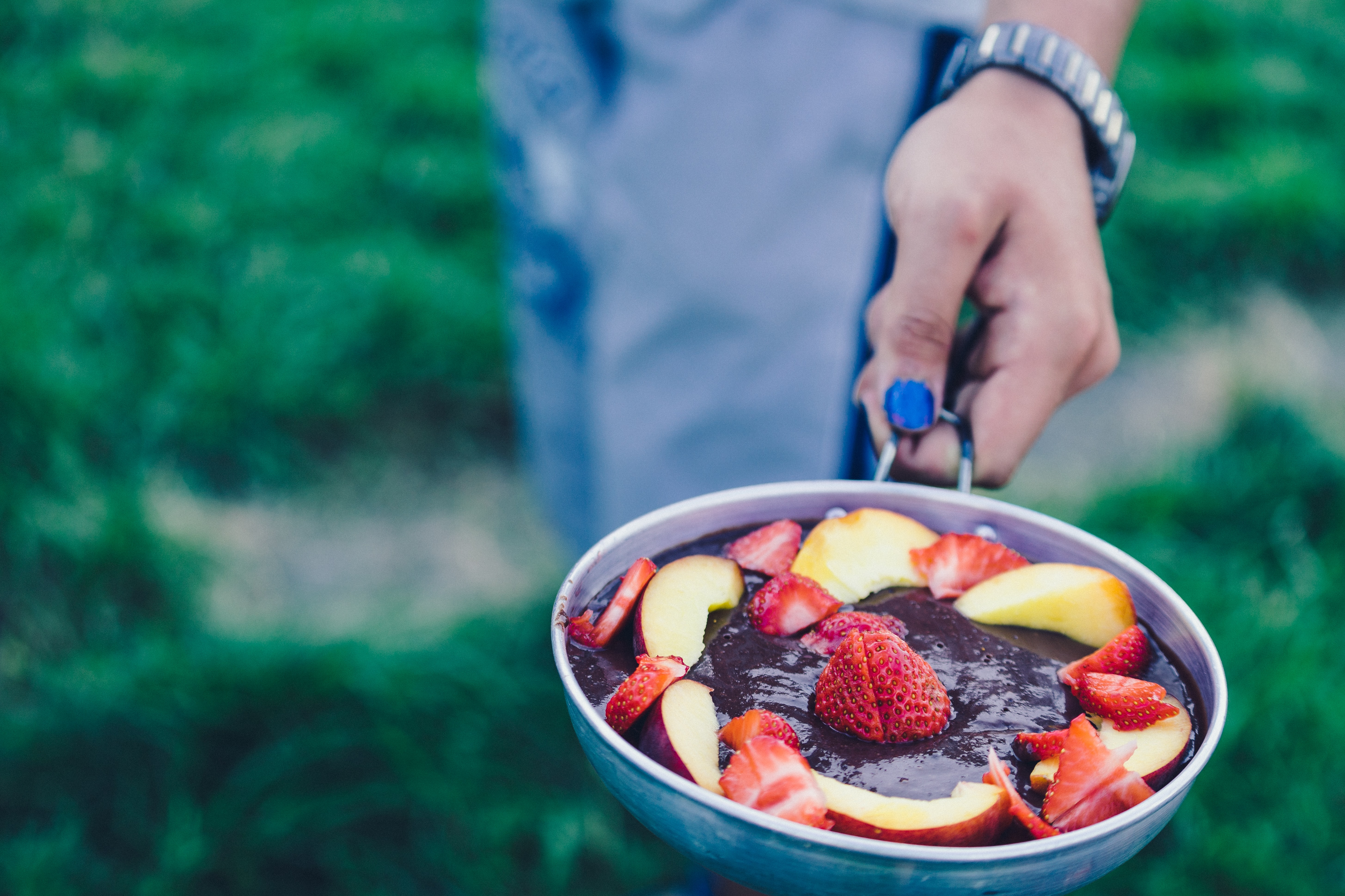 person holding pan filled with sliced strawberries