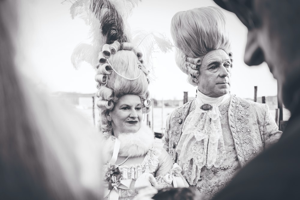Black and white shot of woman and man in traditional aristocratic costumes in San Marco