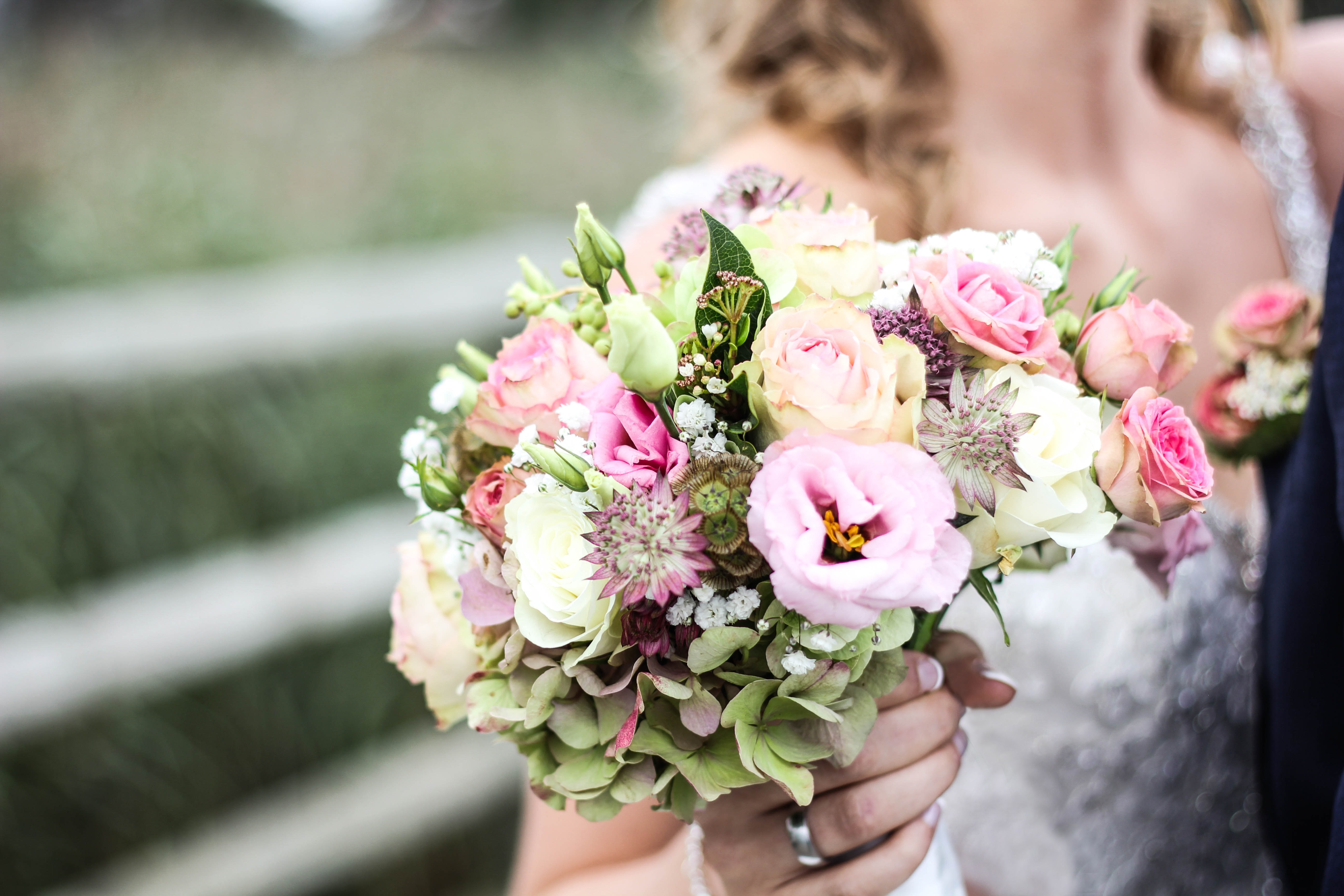 A bride holding a bouquet with pink roses and other delicate flowers
