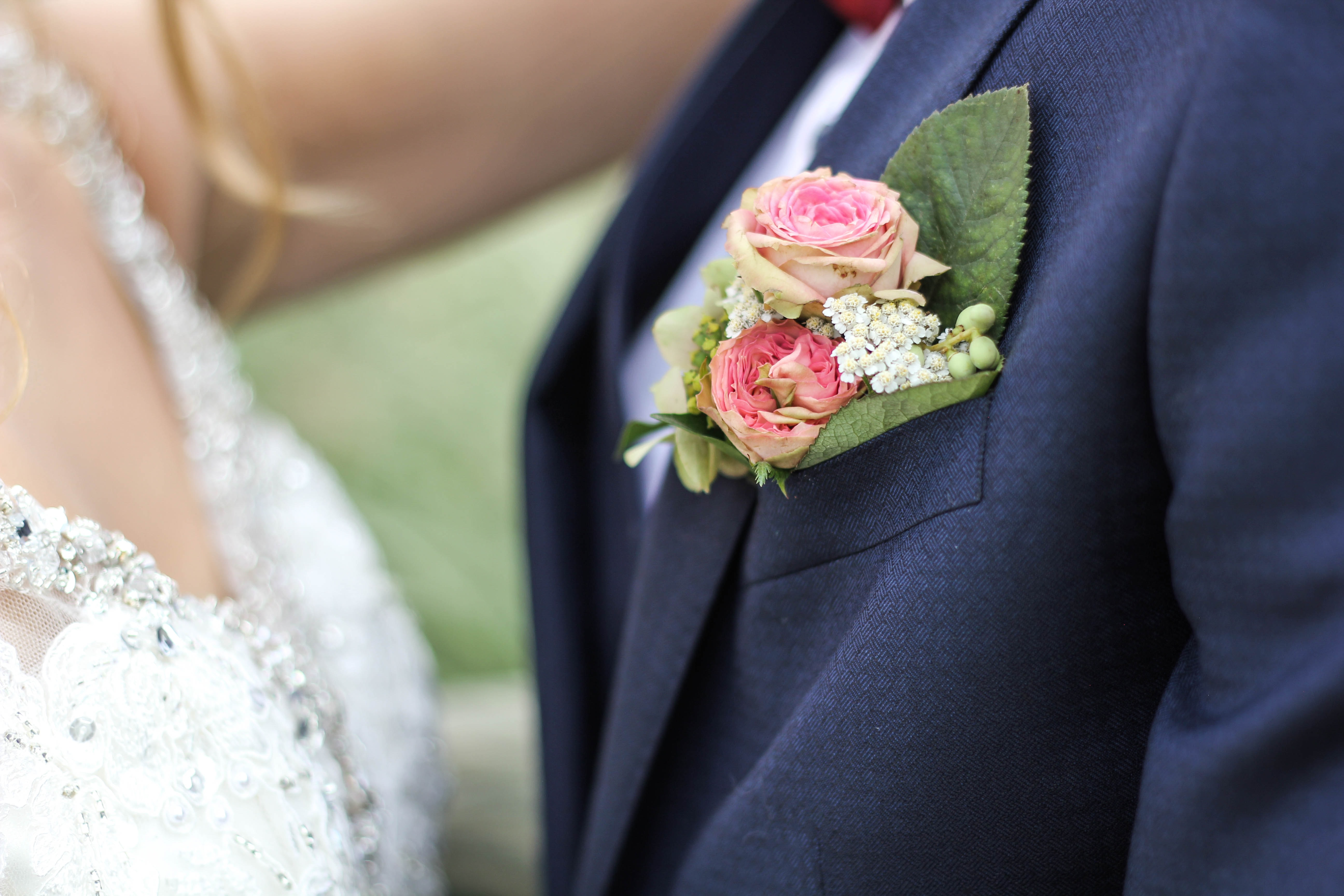 A small bouquet of roses and tiny white flowers in the buttonhole of a groom's suit
