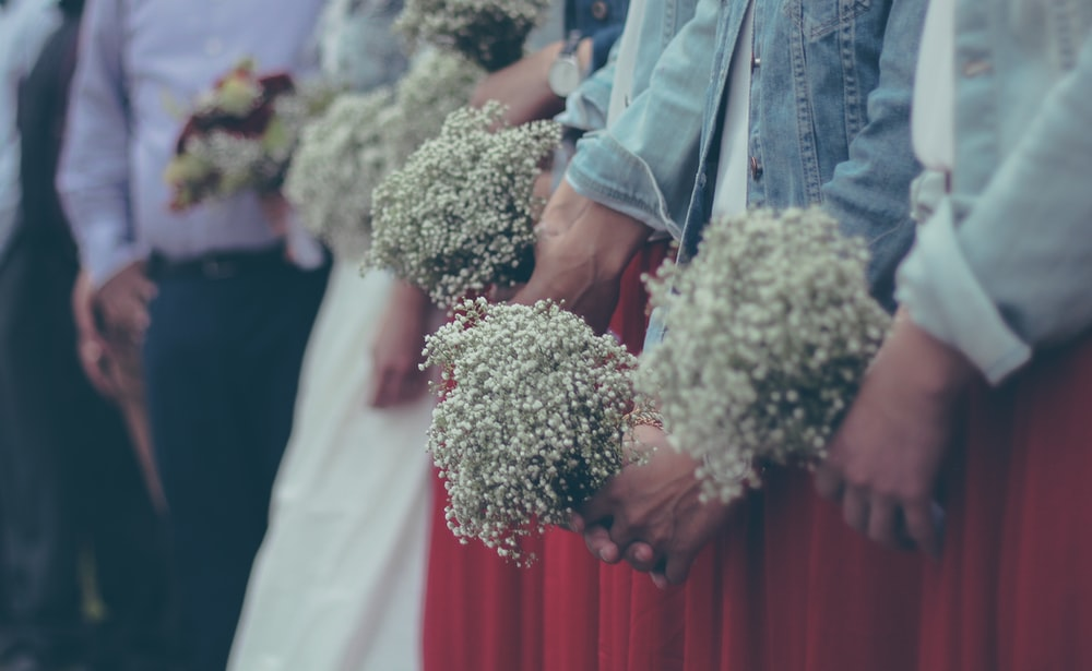 people holding a bouquet of baby's breath flower