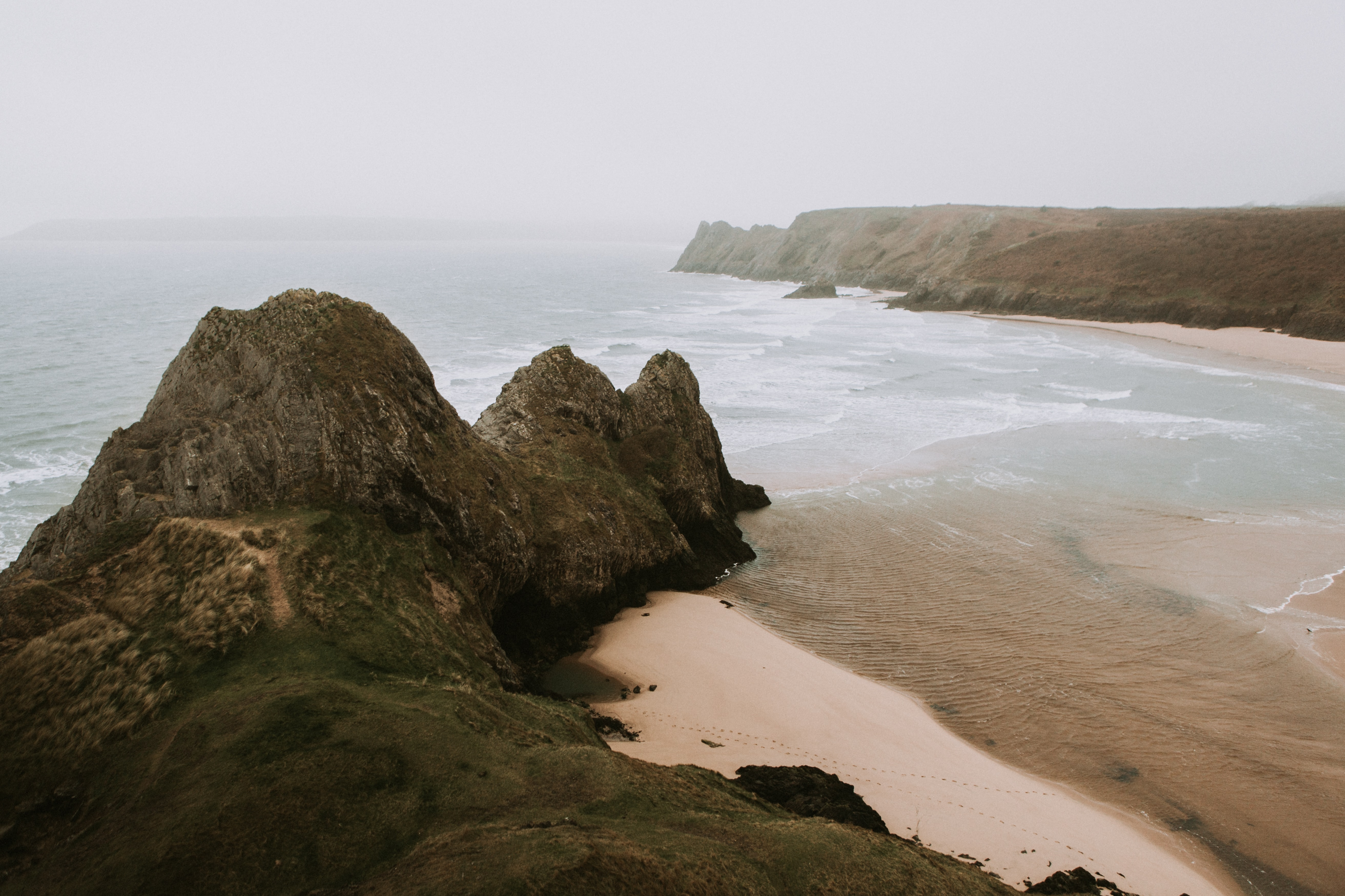 View of the ocean bay on a cloudy day at Three Cliff Bay