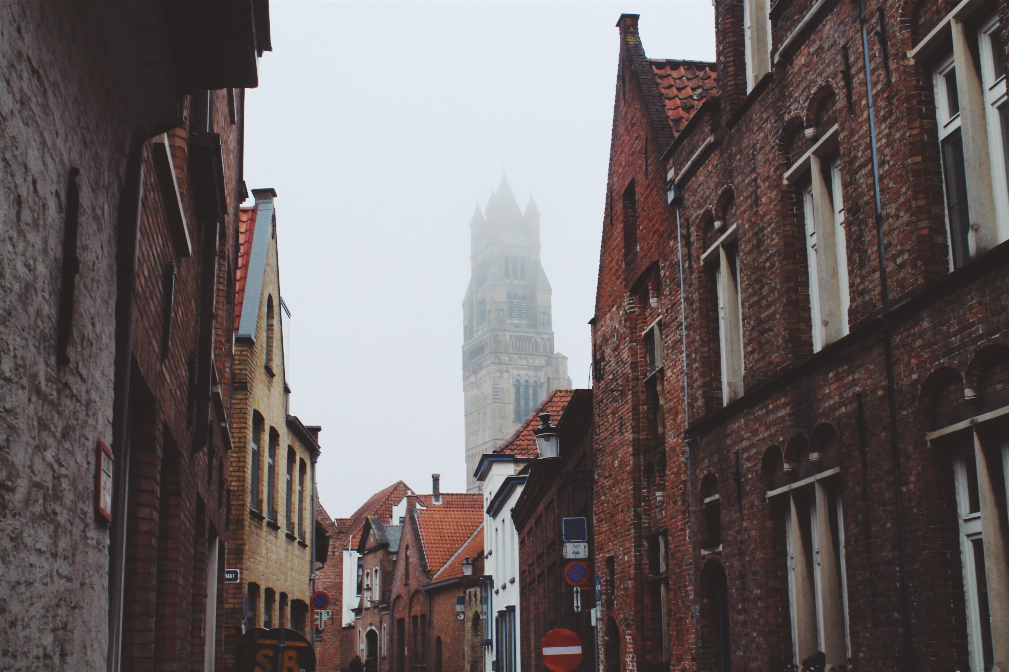 A street in Bruges with brick houses and a church covered in fog in the background