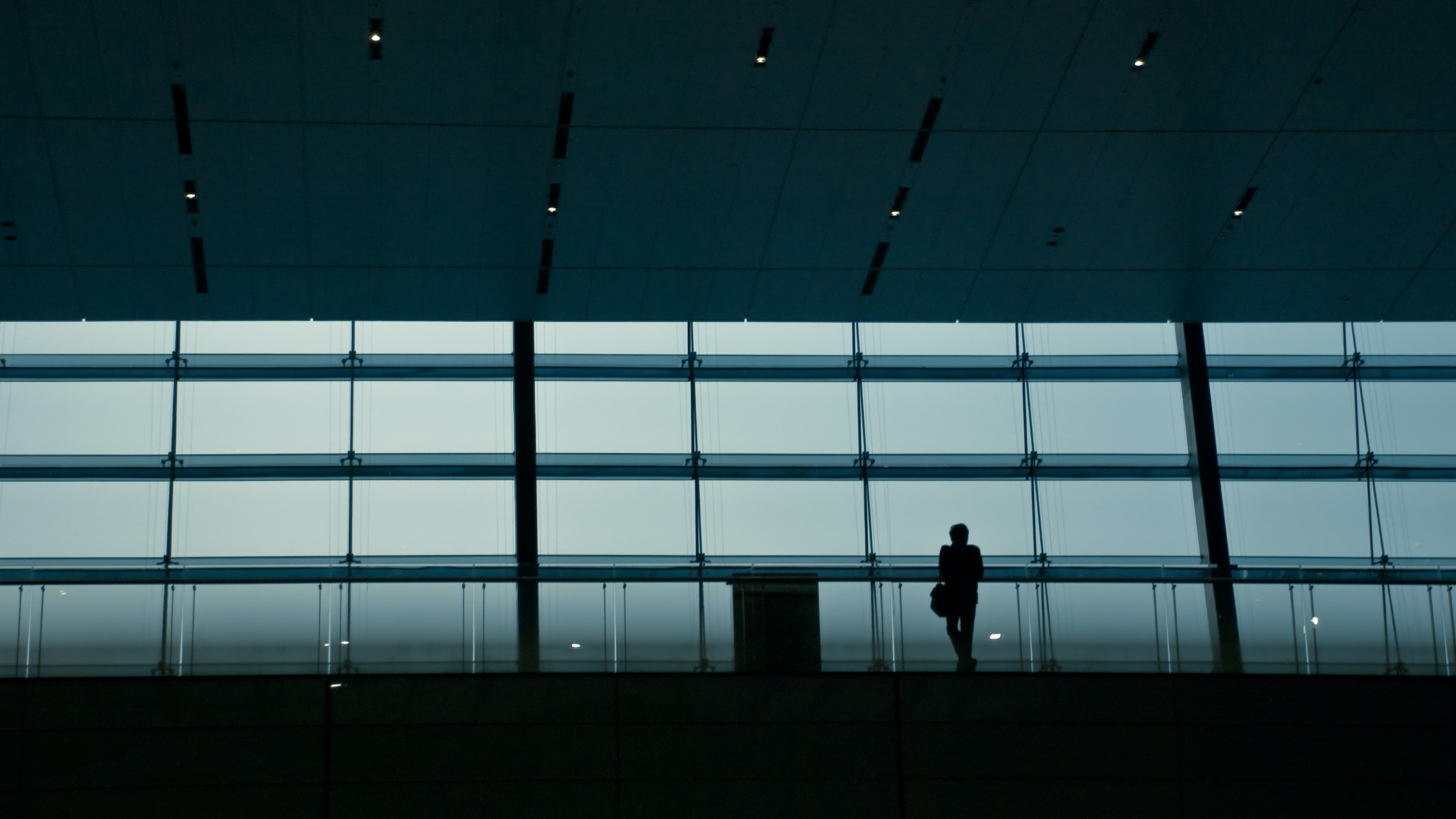 A silhouette of a person in a dark railway terminal