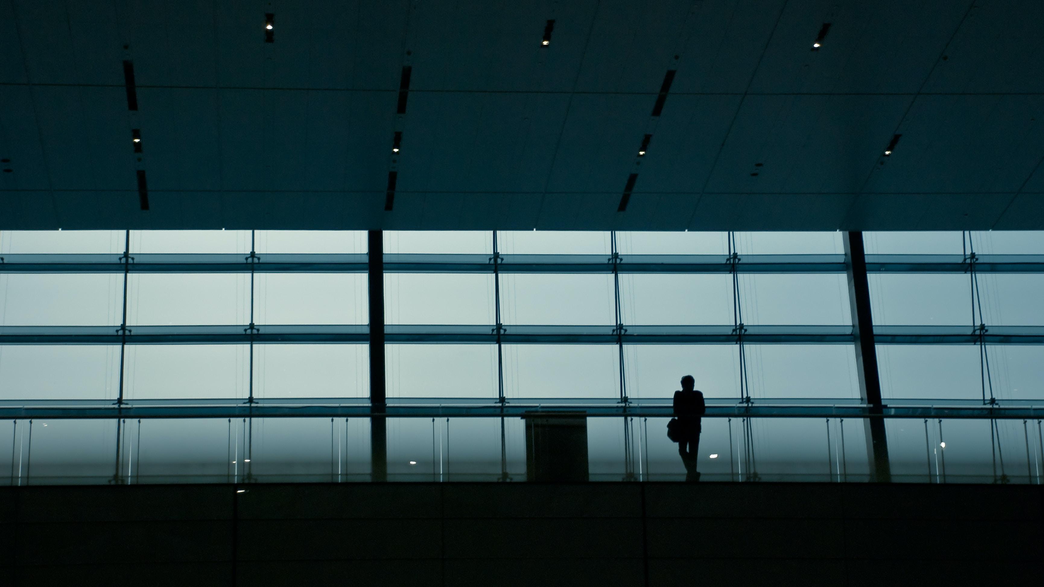 A silhouette of a person in a dark railway terminal