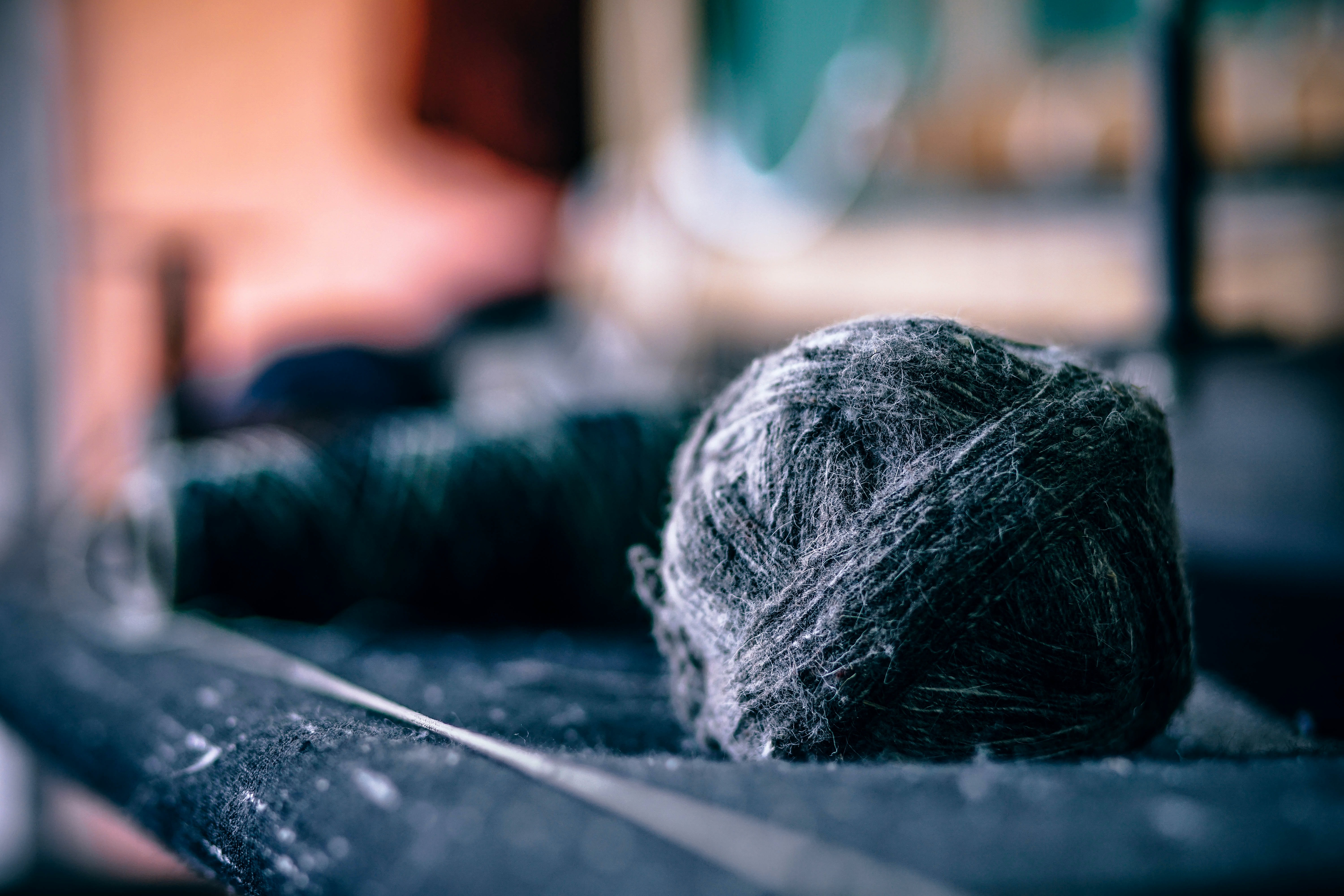 A ball of yarn besides spools of thread and fabric