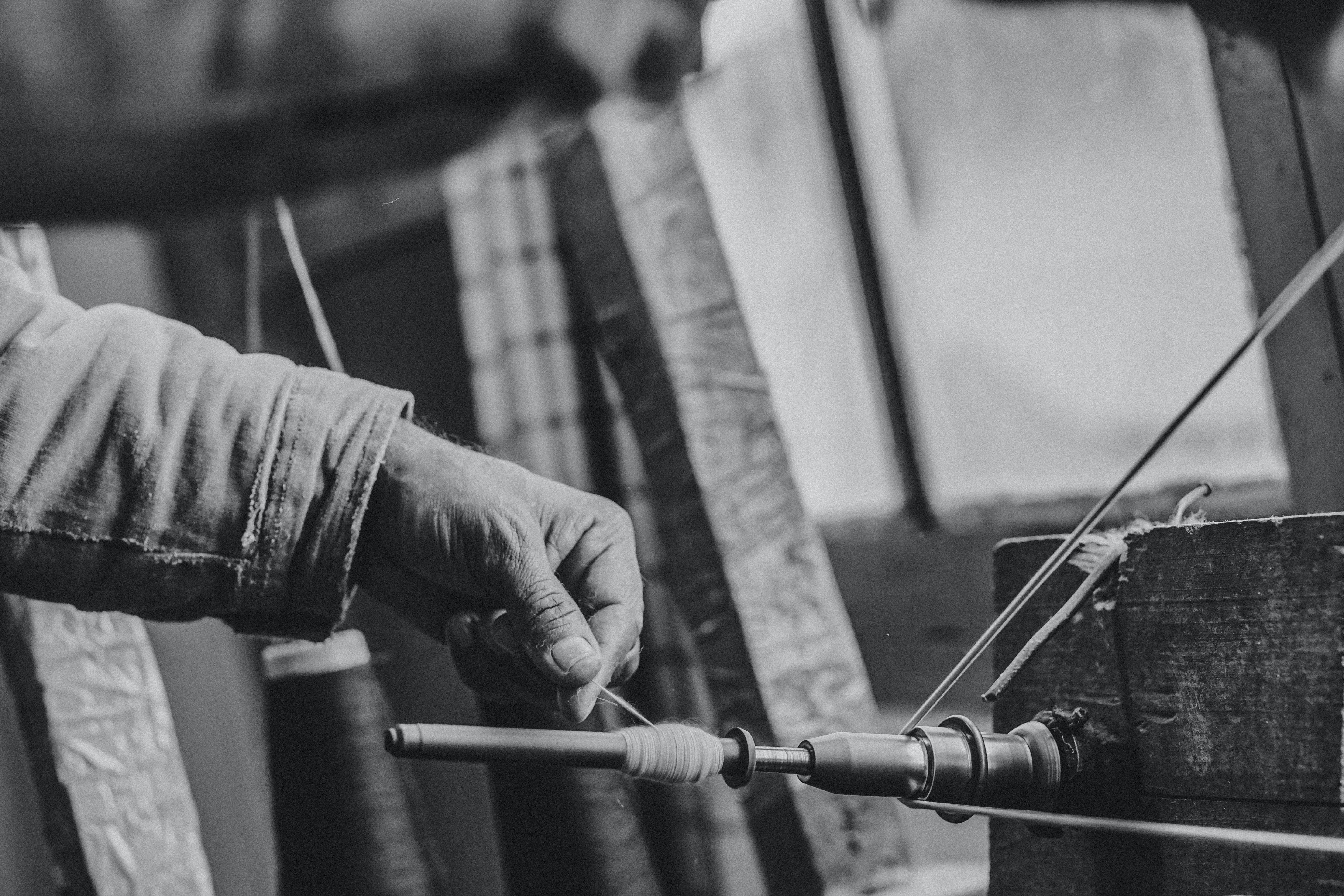 A black-and-white shot of a person spinning thread