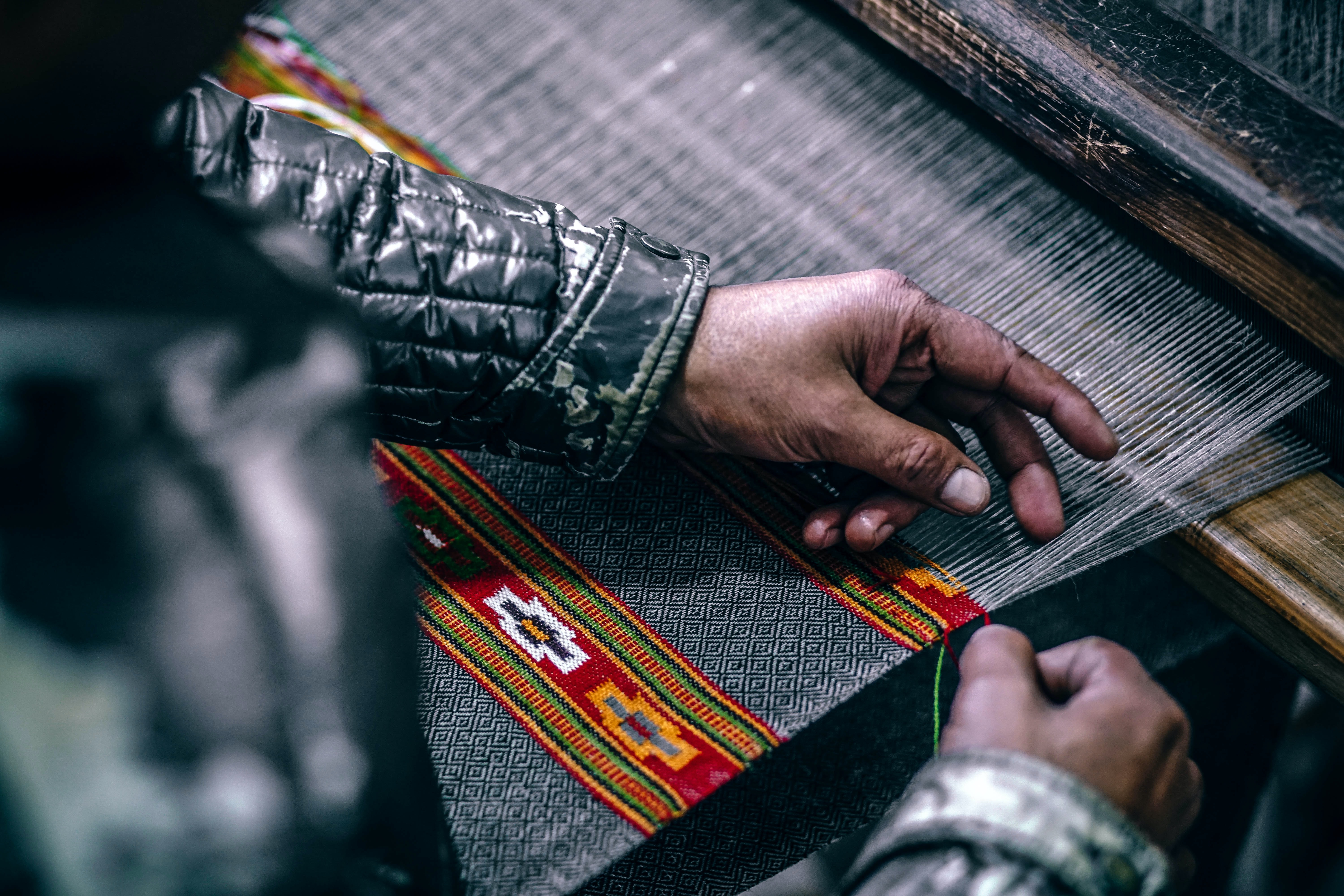 A person wearing a black quilted jacket weaving thread to create a textile on a loom in Manu Temple Road