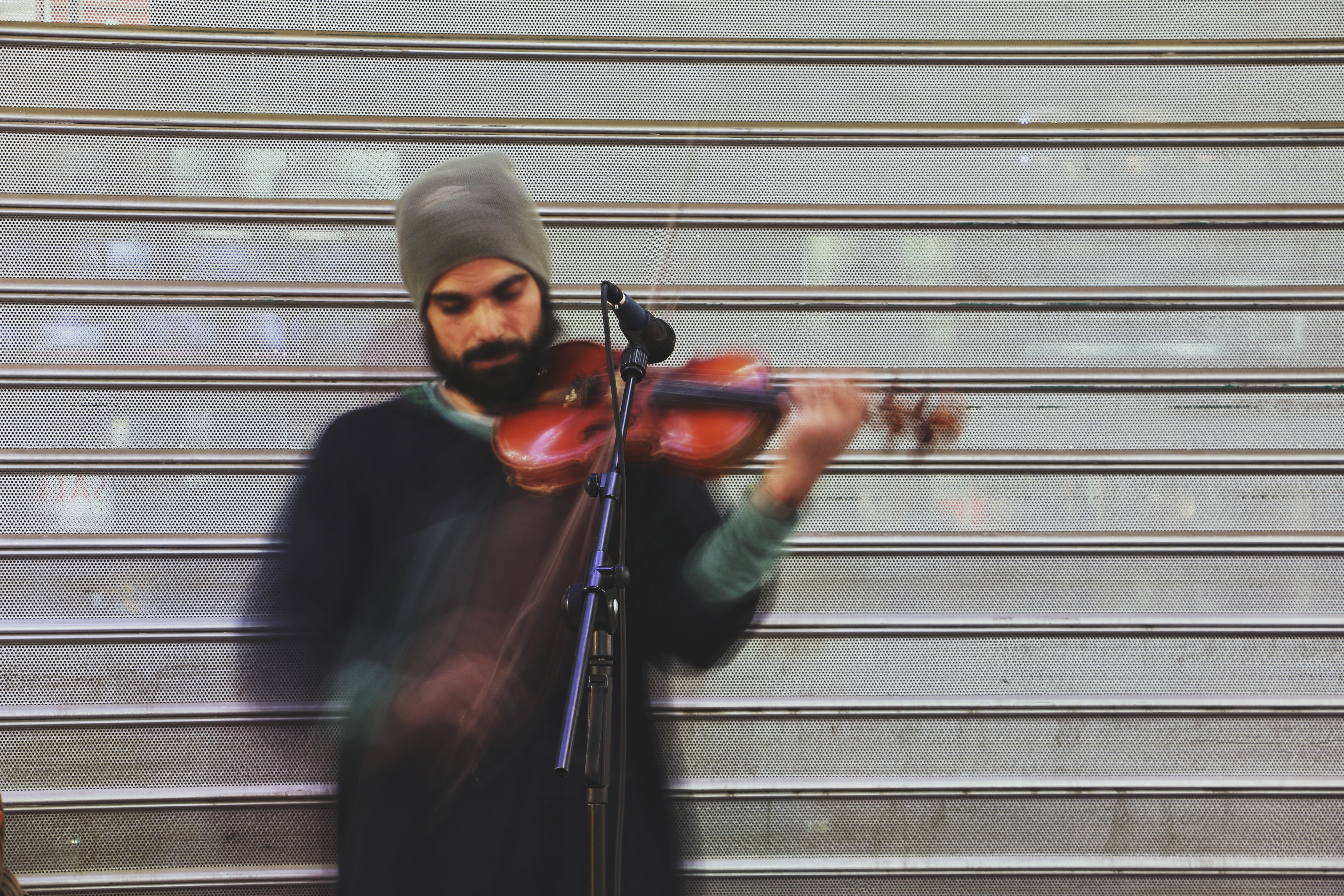 A bearded man in a beanie playing a violin next to a microphone in Golestan Shopping Center