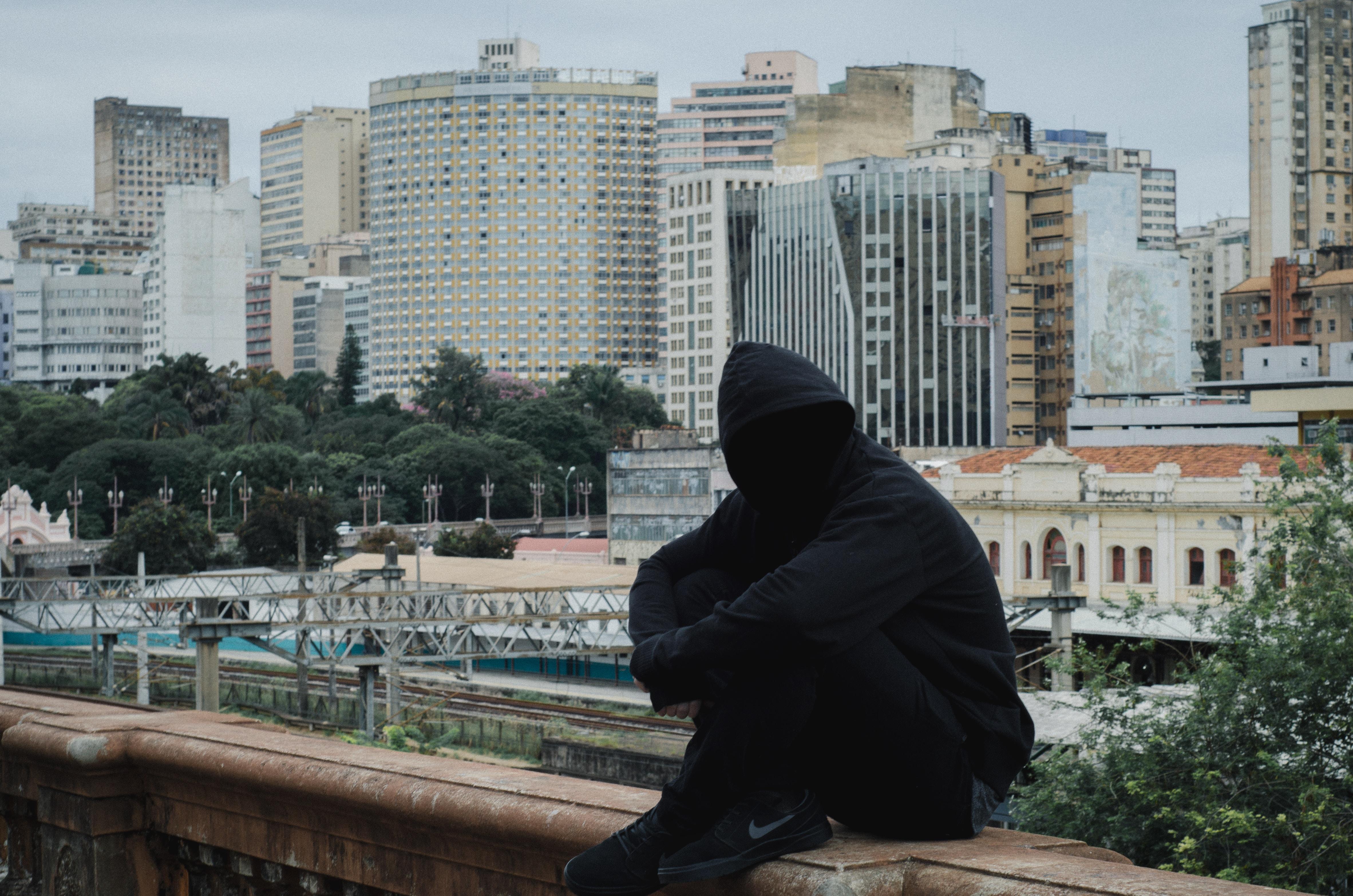 man wearing hooded jacket sitting on beige concrete