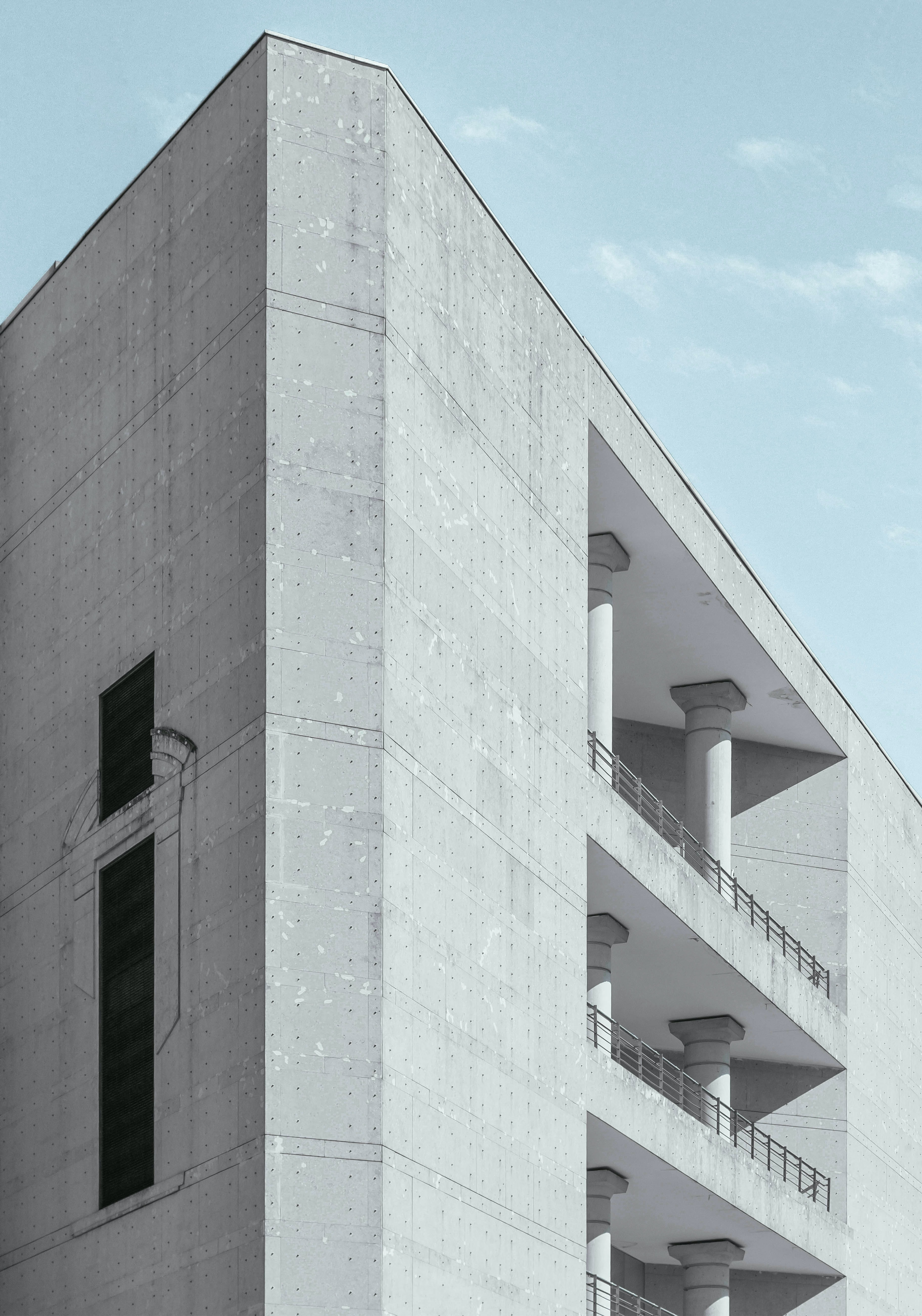 A gray concrete building with columns on its balconies