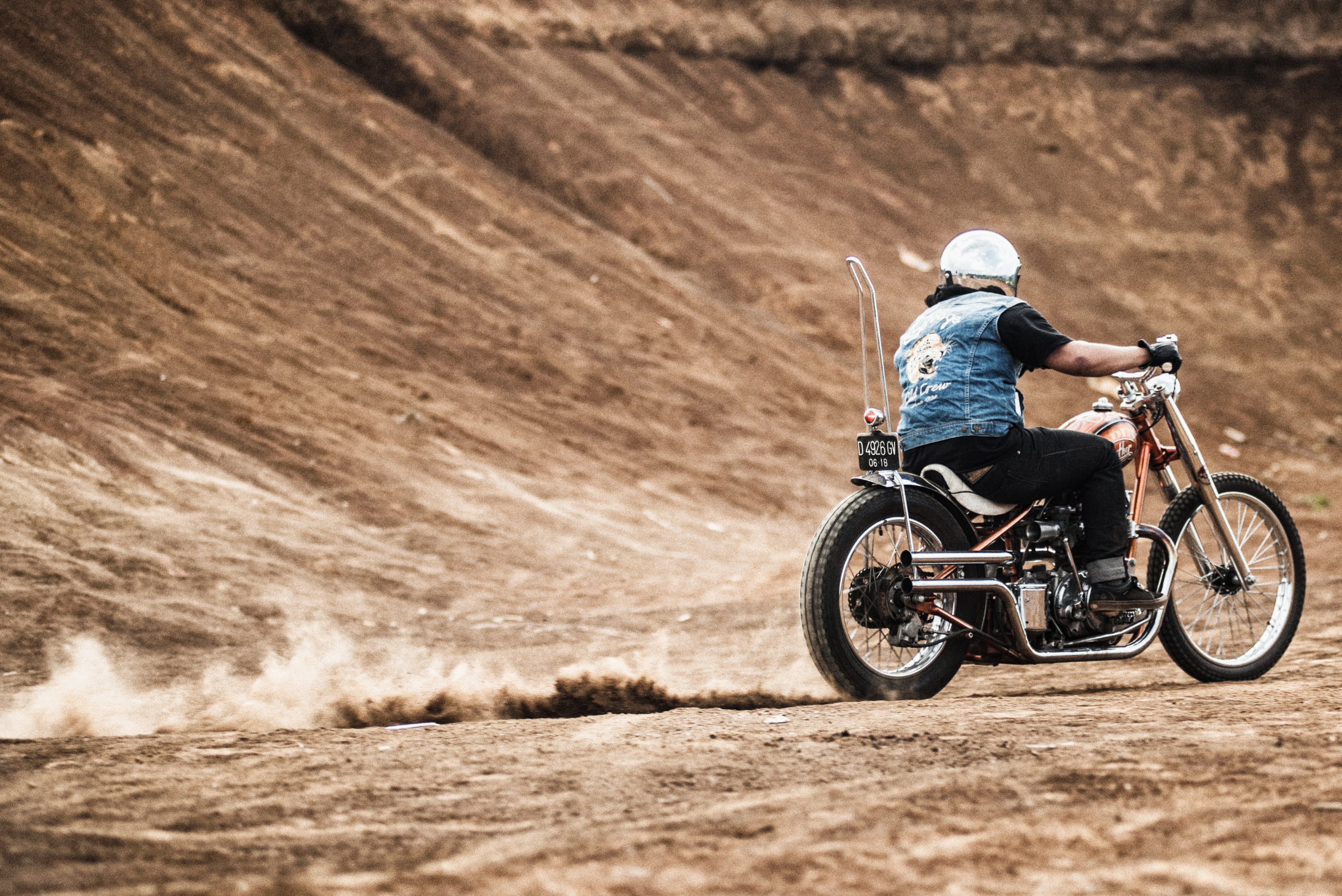 A motorcyclist in a denim jacket and reflective helmet riding his bike and leaving a trail of dust by a dirt mound