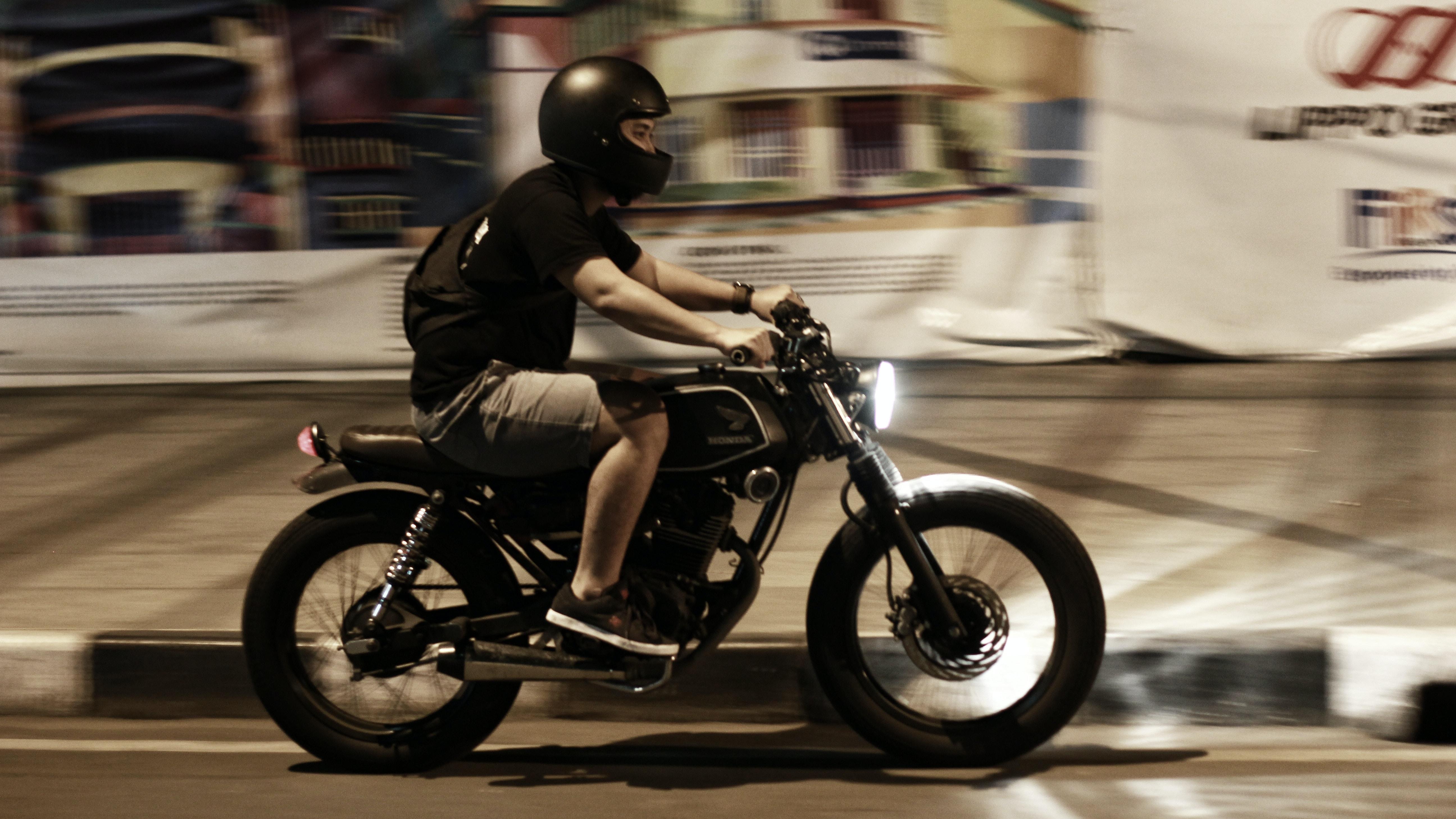 A man in a black helmet on a motorbike in artificial light