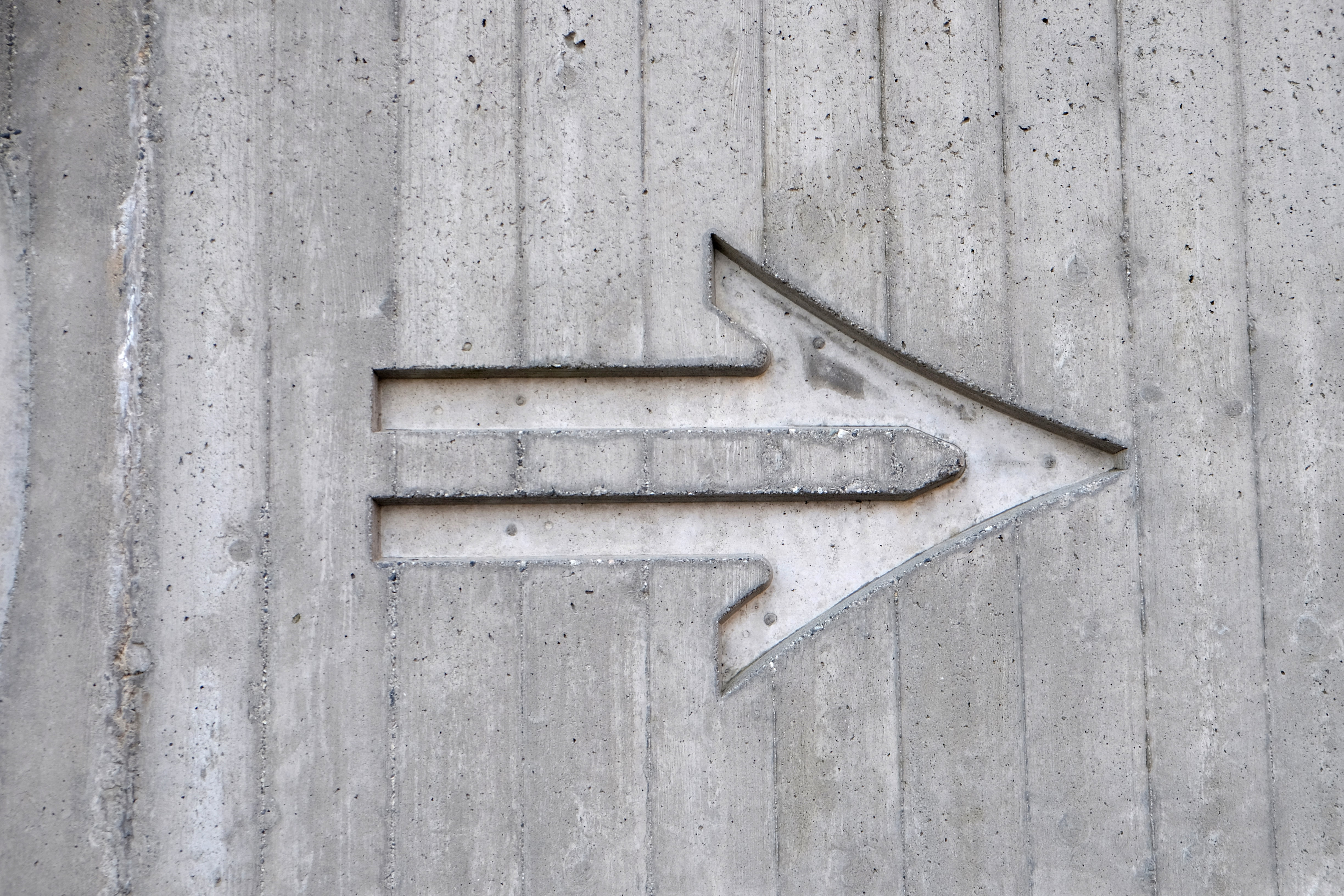 An arrow etched in a concrete wall