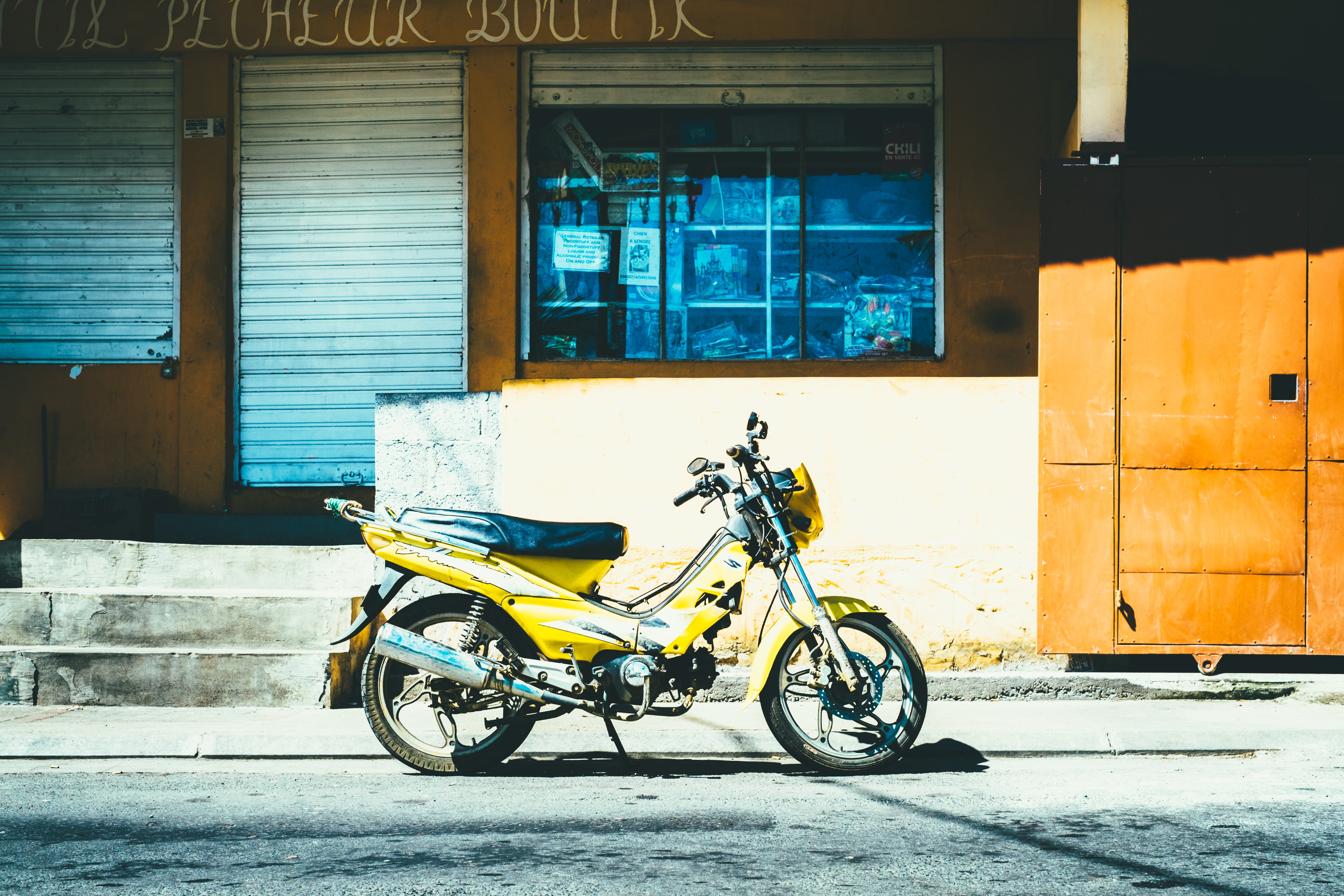 A yellow motorcycle parked outside a closed store with stone steps and steel shutters