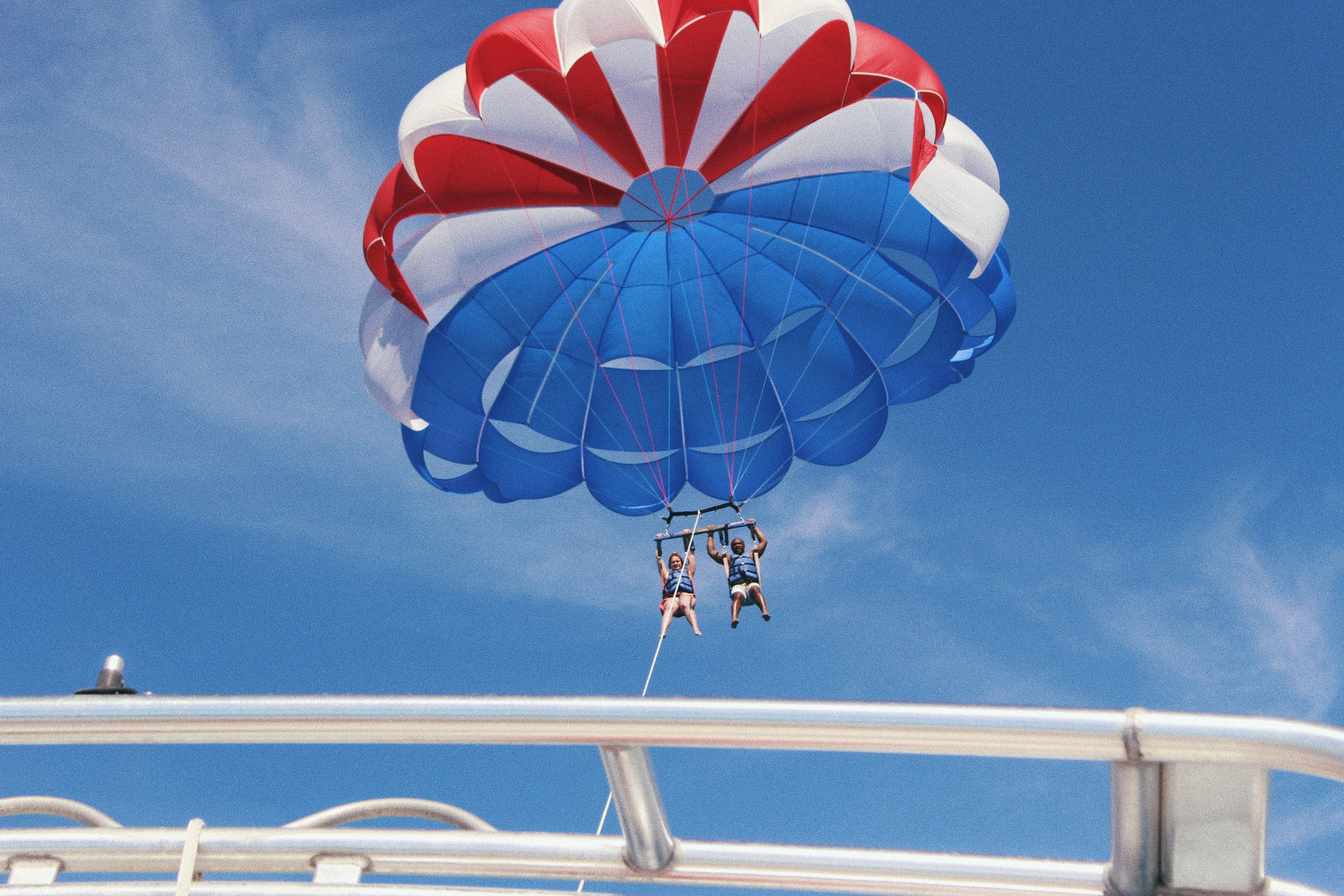People parasail with a parachute behind a boat on a bright blue day